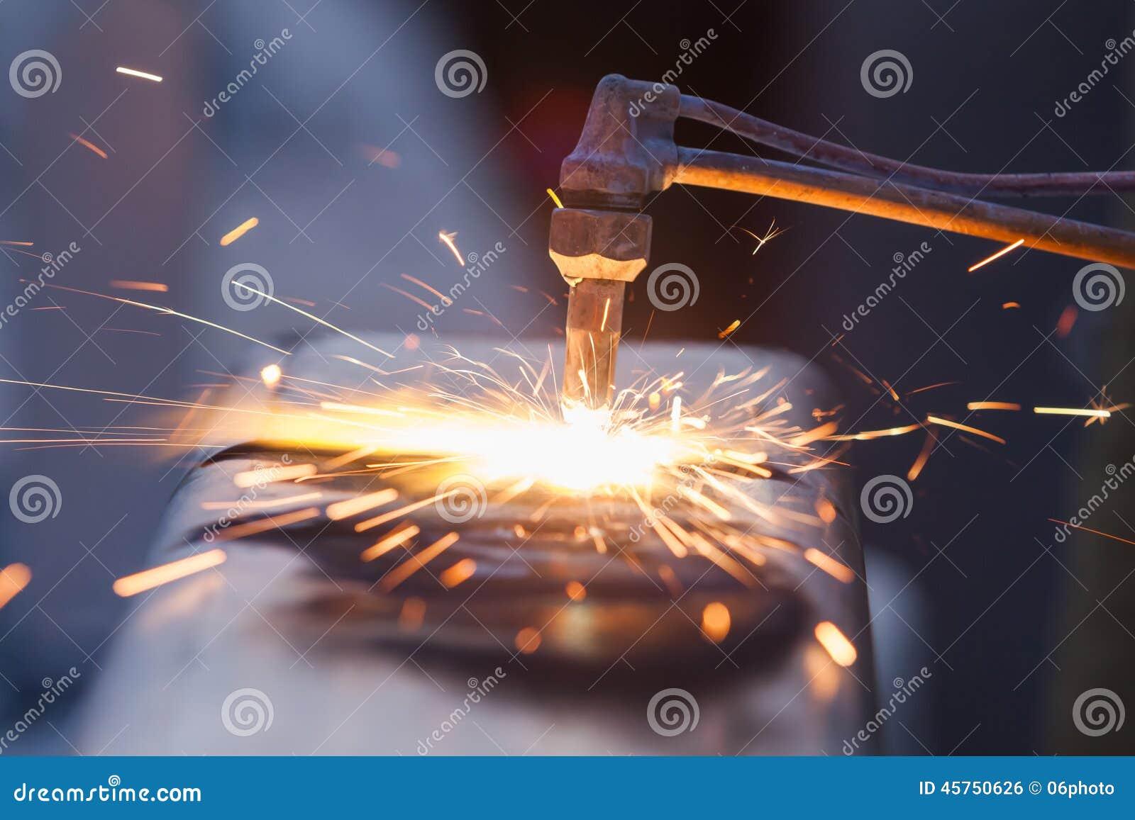 O trabalhador que corta a tubulação de aço usando a tocha do metal e instala a borda da estrada