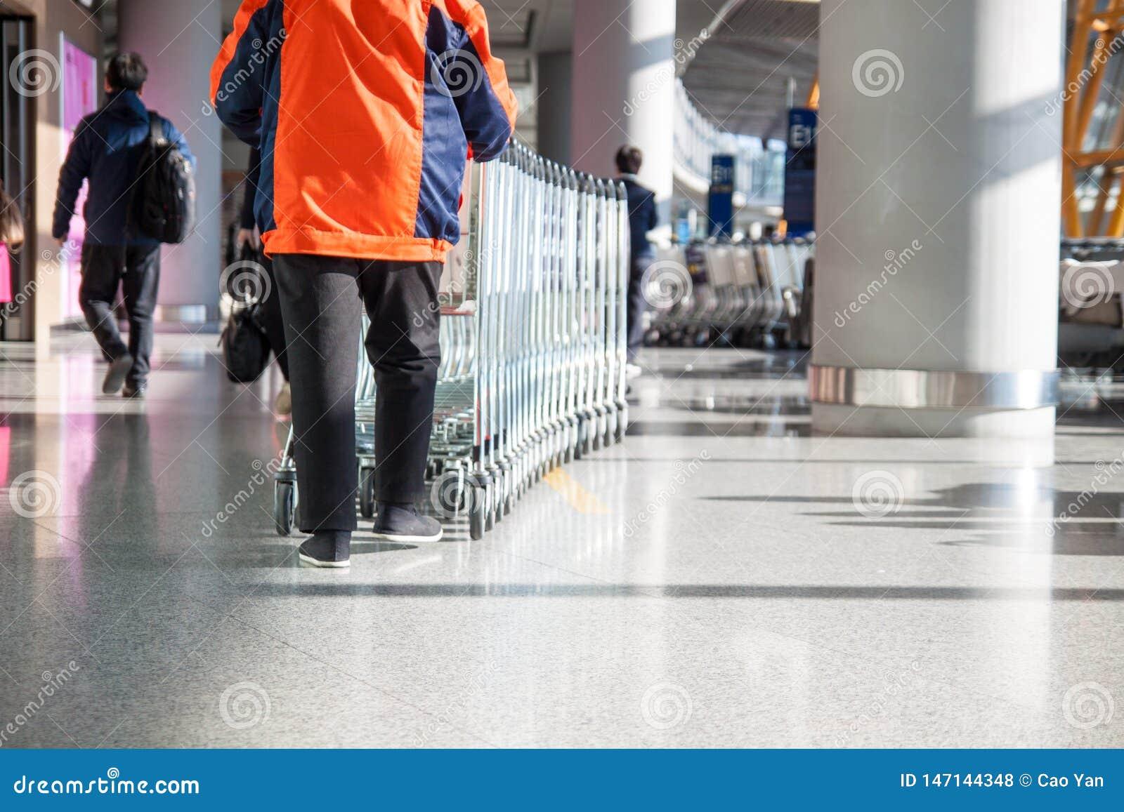 O trabalhador rola uma pilha de troles da bagagem na área da partida do aeroporto