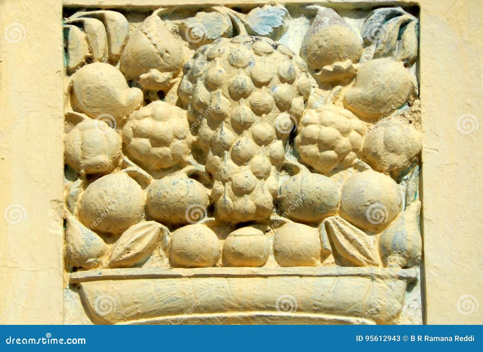 O trabalho do estuque da arte da parede dos frutos na cesta projeta em exteriores do templo das pessoas de 200 anos