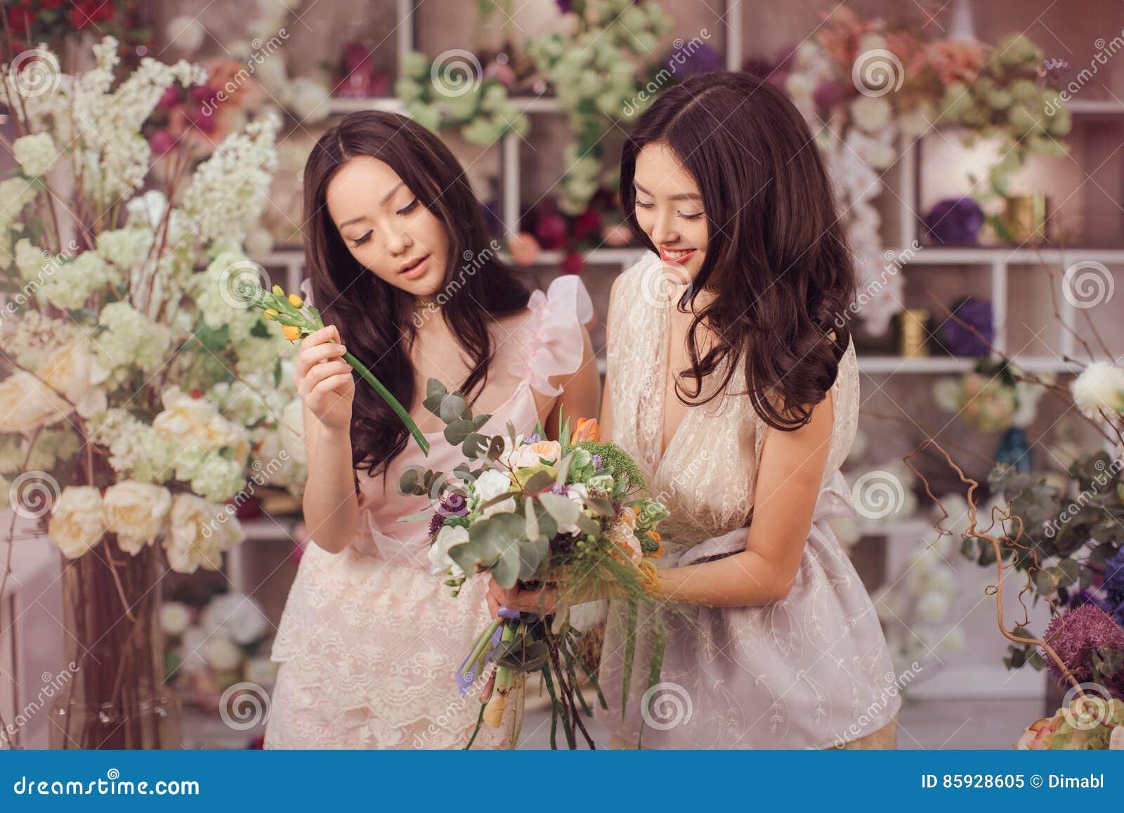 O trabalho feliz dos floristas asiáticos bonitos das mulheres na loja de flor com muita mola floresce