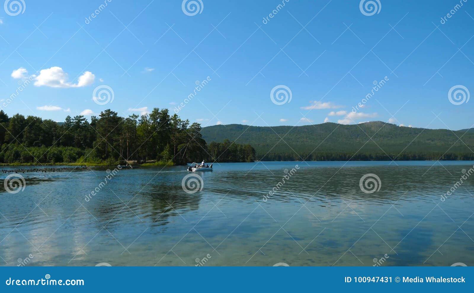 O transporte do barco no rio, monta abaixo de um rio tropical bonito, grupo de povos felizes no lago Barco a motor com