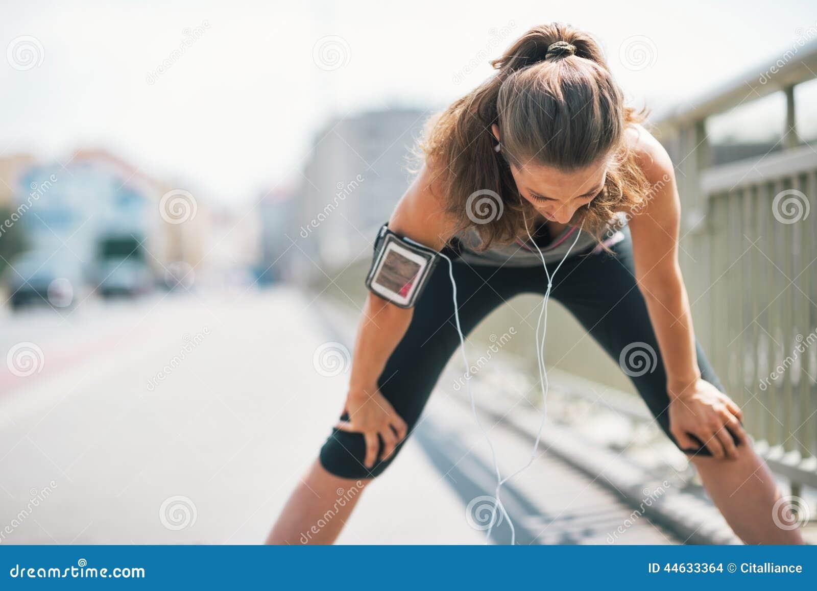 O travamento cansado da jovem mulher da aptidão respira