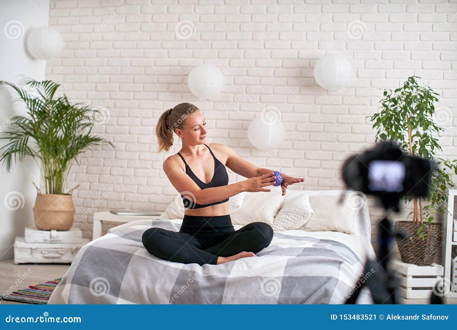 O treinador em linha do córrego mostra a bola da massagem do exercício da técnica abrandamento dos músculos da mão com uma bola d