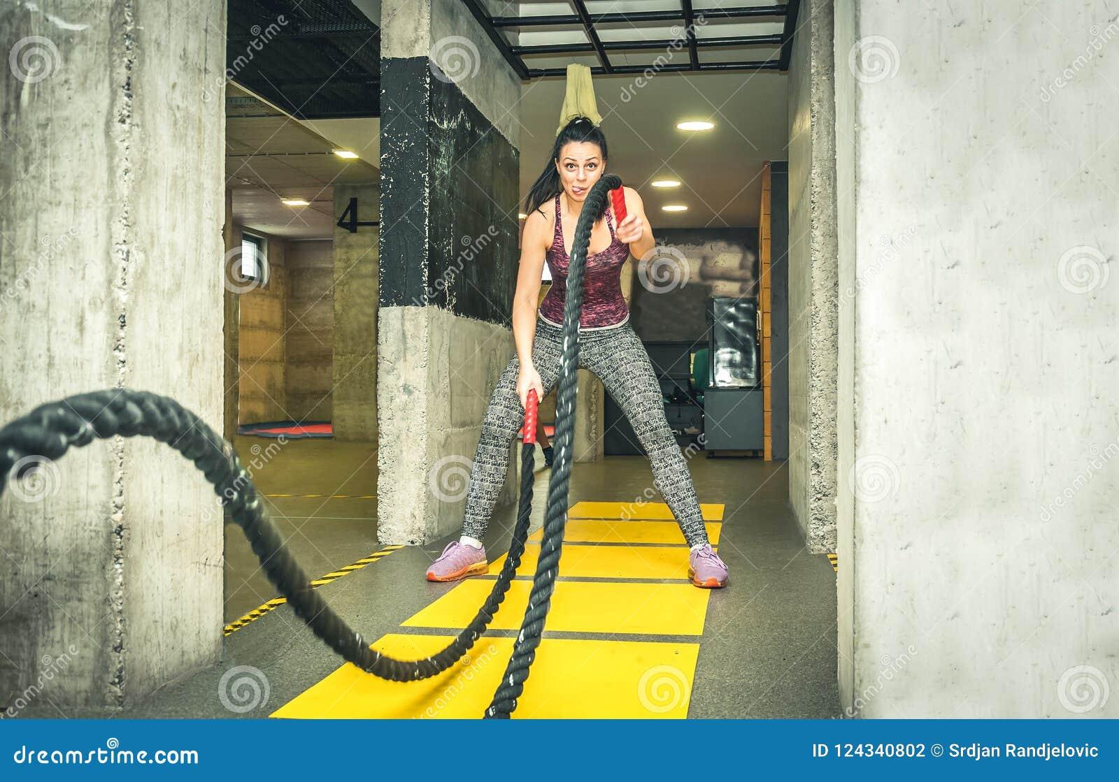 O treinamento da menina nova e atrativa bonita que faz o divertimento e as caras engraçadas quando malhar na batalha ropes no gym