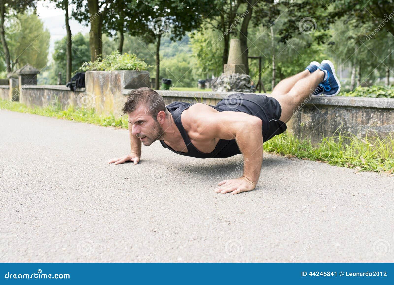 O treinamento do homem e o exercício de fazer empurram levantam no parque