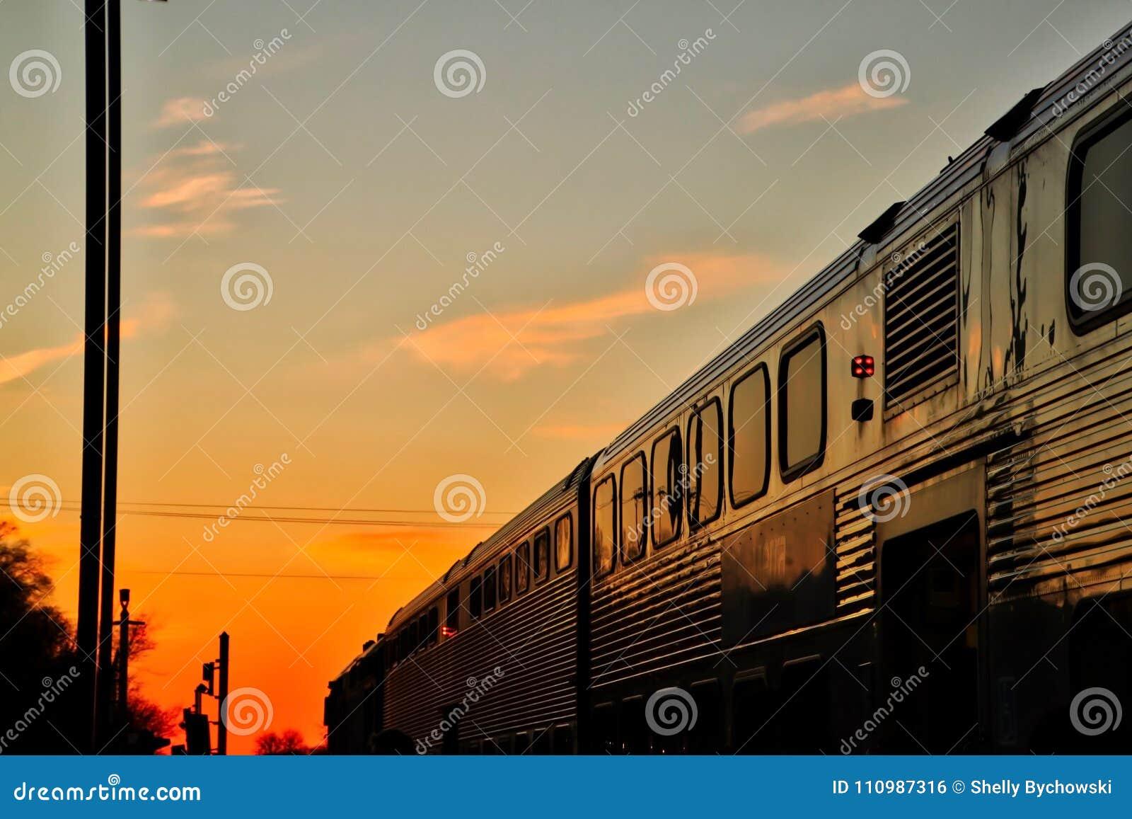 O trem de Metra viaja no por do sol no fim de um dia de inverno atrasado