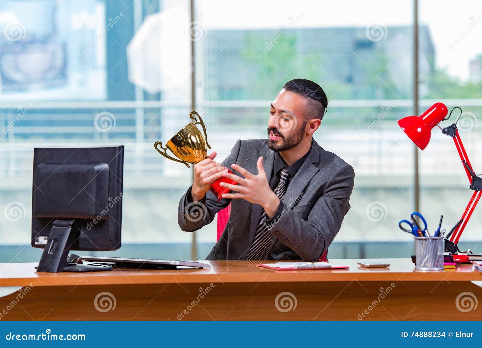 O troféu de vencimento do copo do homem de negócios no escritório