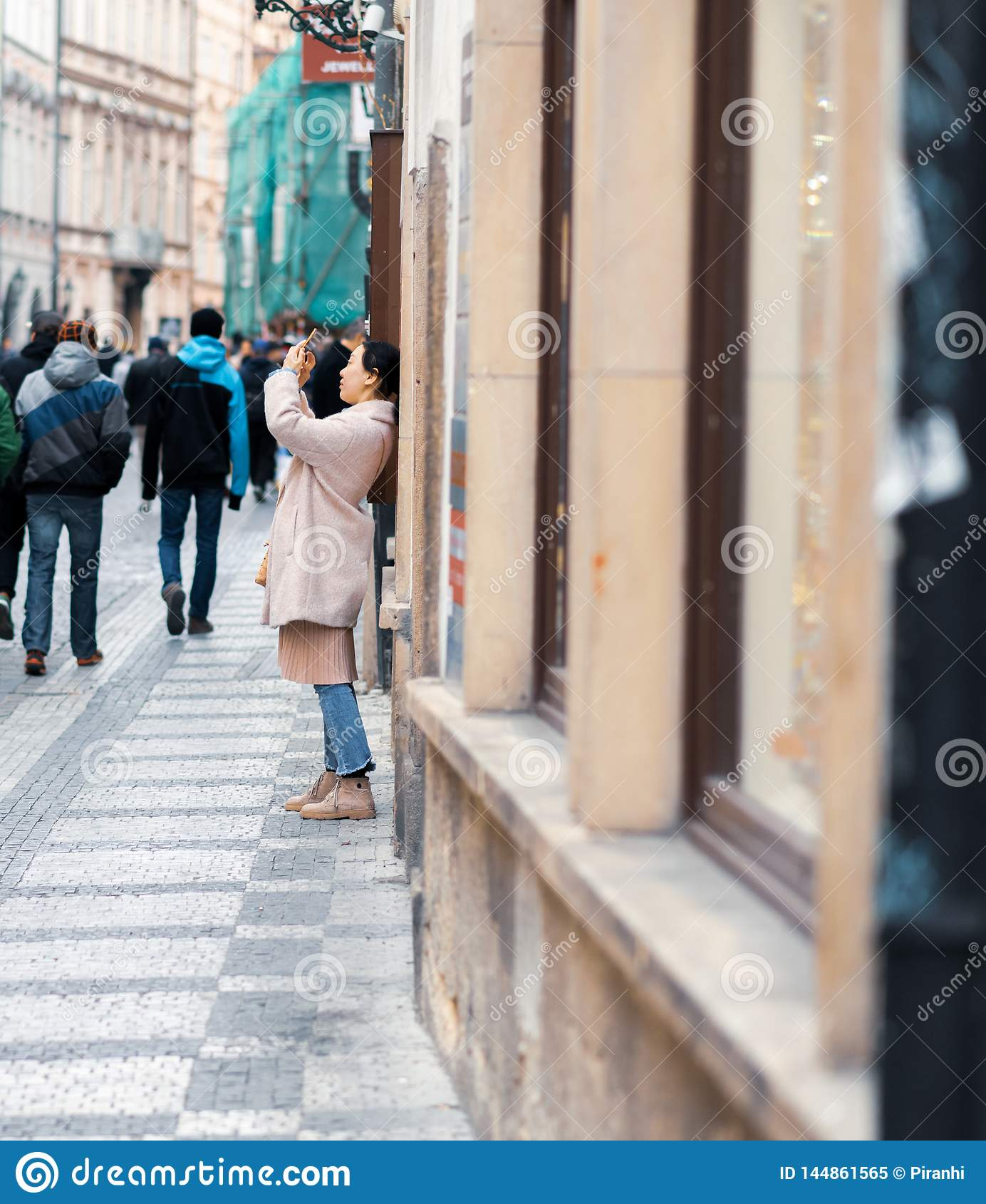 O turista asiático fêmea novo toma fotos enquanto sightseeing em Praga, República Checa - feriados da Páscoa