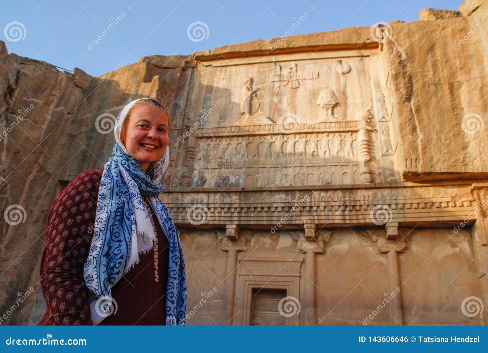 O turista da jovem mulher com uma cabeça coberta está no fundo dos bas-relevos famosos da capital de Persia Iran - P do dia