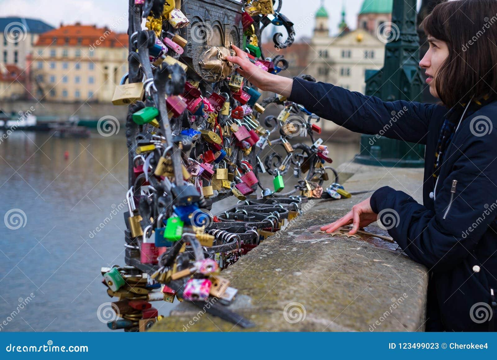 O turista da jovem mulher toca na estátua de St John Nepomuk na ponte de Charles em que há muitos fechamentos que penduram para a