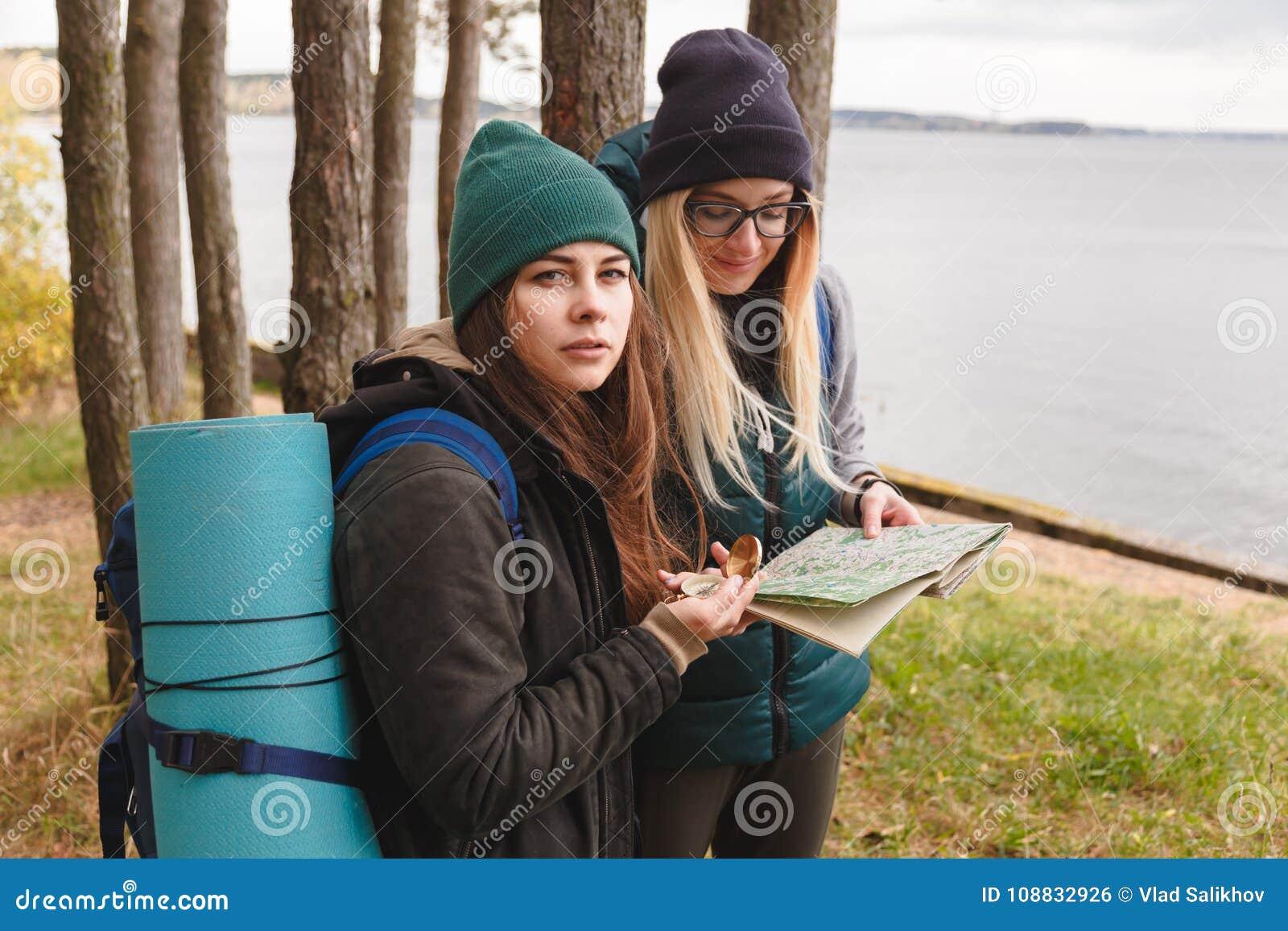 O turista de dois jovens determina o mapa e o compasso de rota