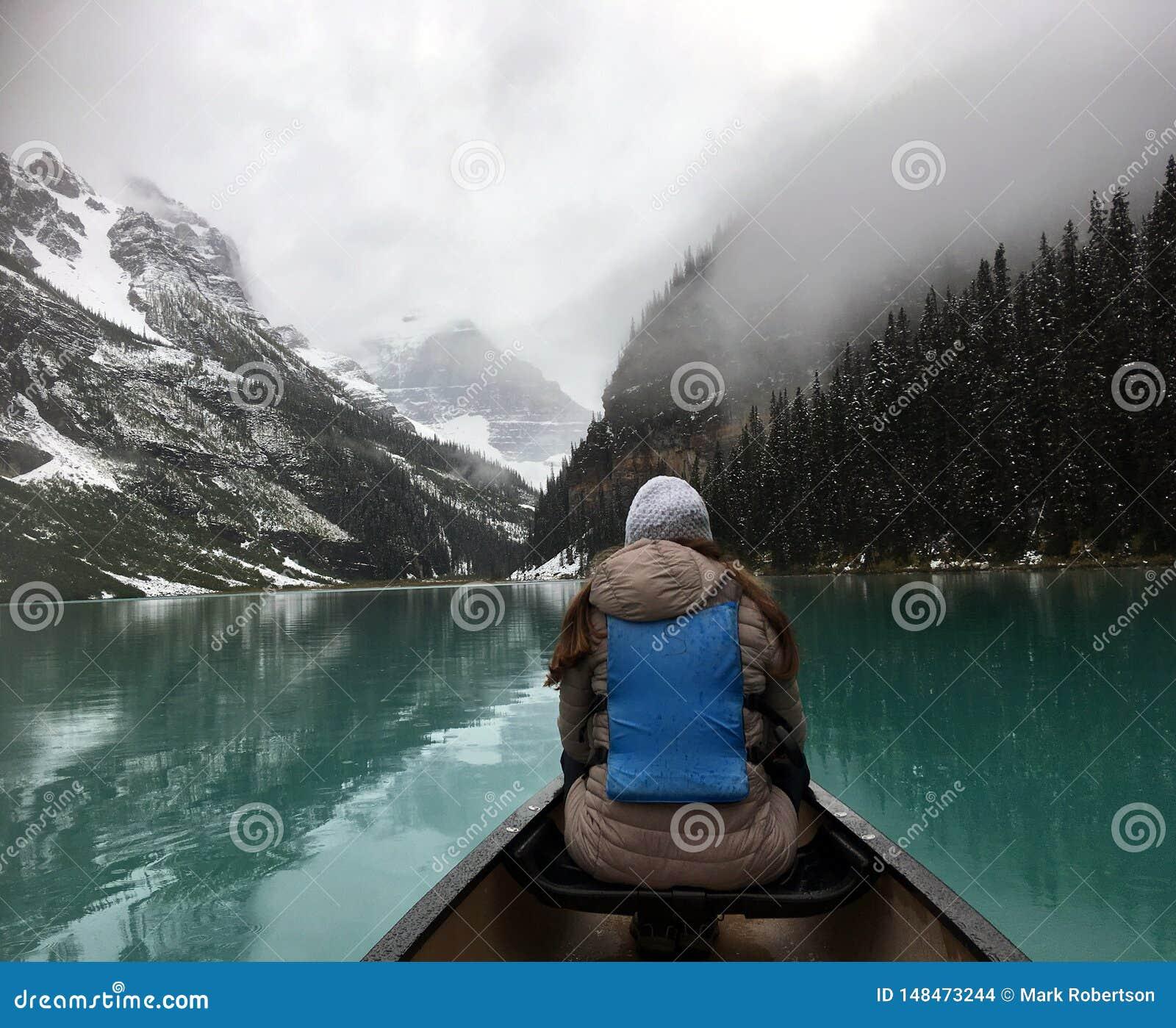 O turista f?mea aprecia a vista de um caiaque em Lake Louise