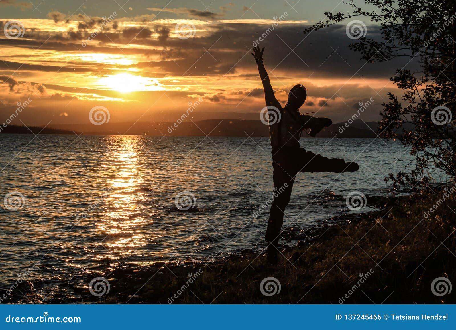 O turista novo do indivíduo salta e aprecia um por do sol bonito sobre o lago Os midges voam em torno dele, que incandesce nos ra