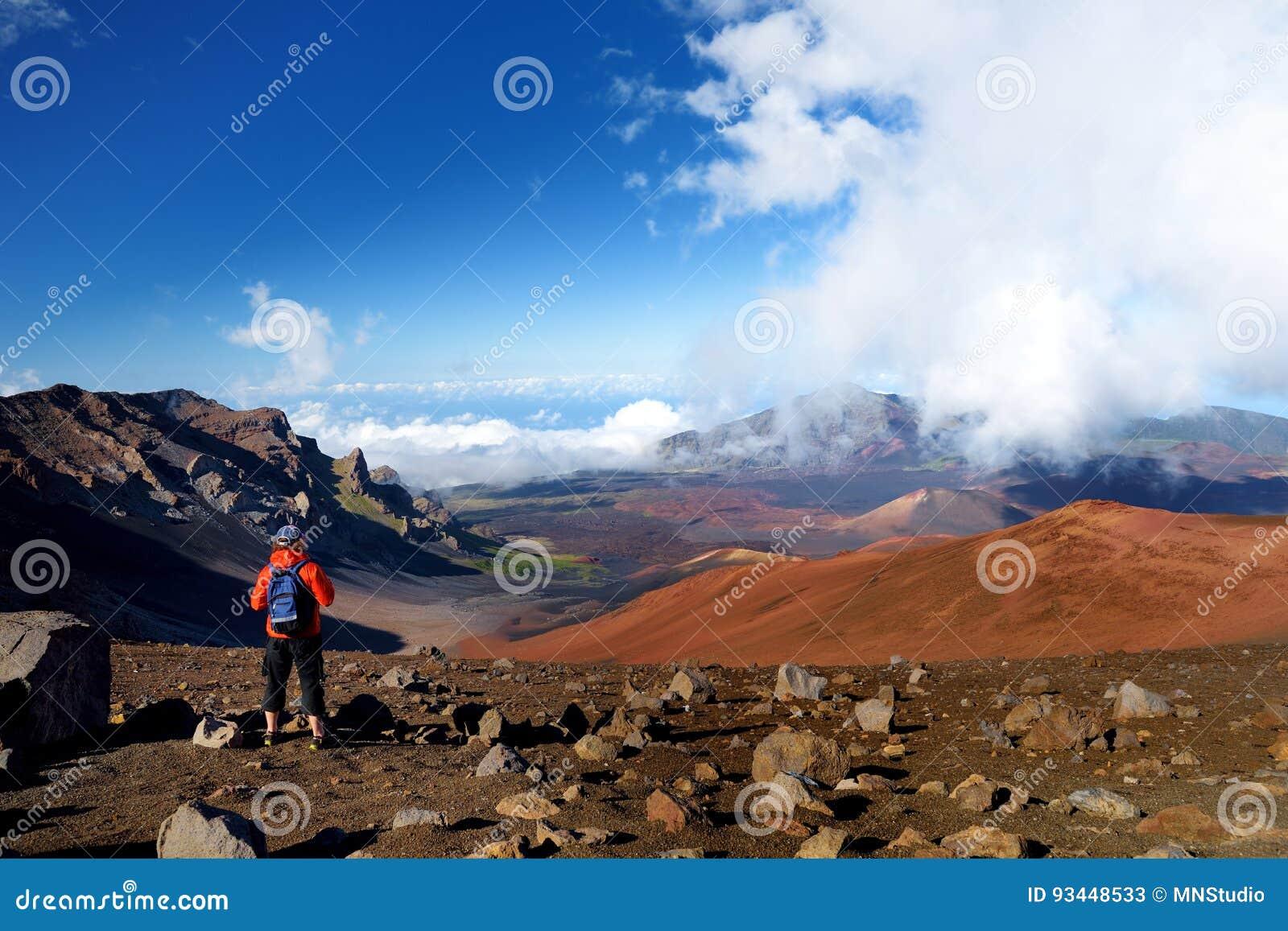 O turista que caminha na cratera do vulcão de Haleakala nas areias deslizantes arrasta