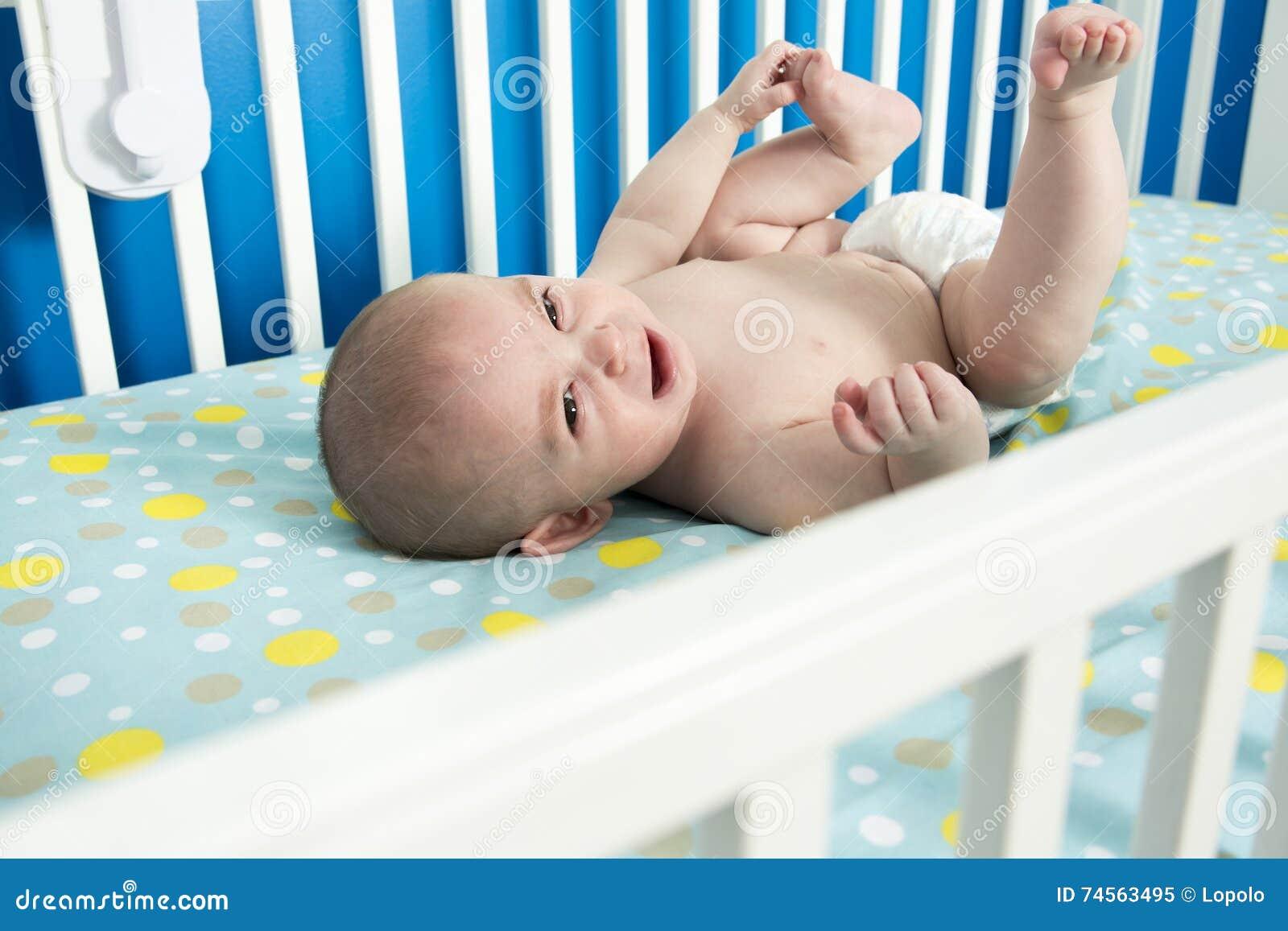 O um bebê recém-nascido idoso bonito do mês está colocando nela para trás na ucha, gritando