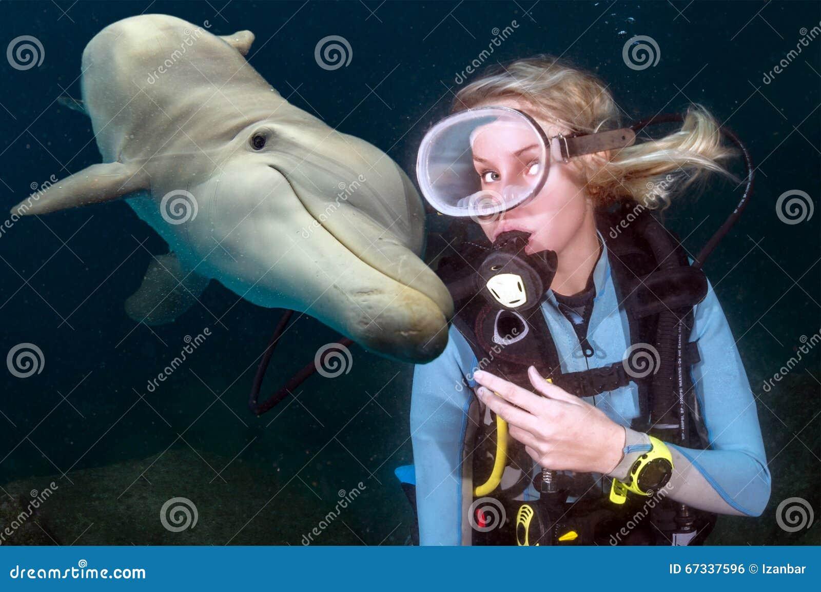 O underwater do golfinho encontra um mergulhador de mergulhador louro