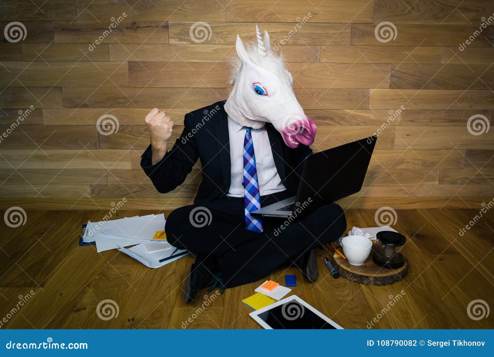O unicórnio irritado e descontentado em um terno e em um laço mostra o punho e trabalha em casa o escritório