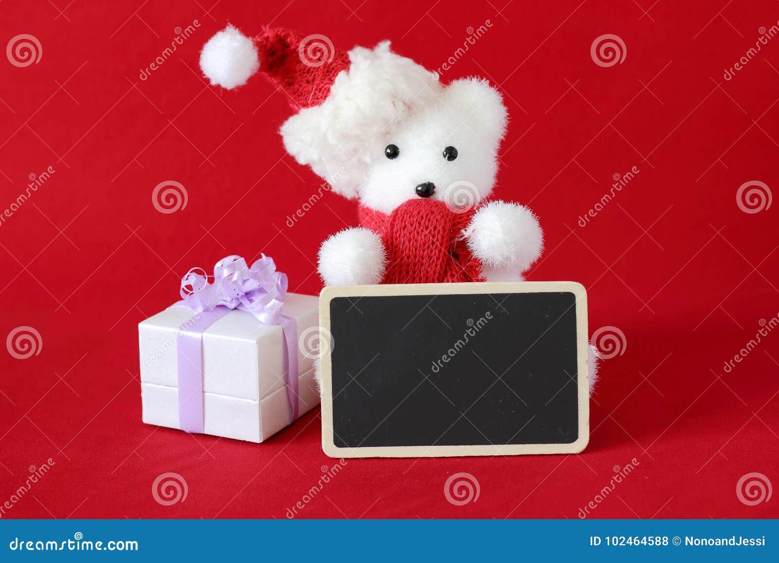 O urso polar que vestem um chapéu e um lenço vermelho para a decoração da festa de Natal com uma mensagem vazia slate