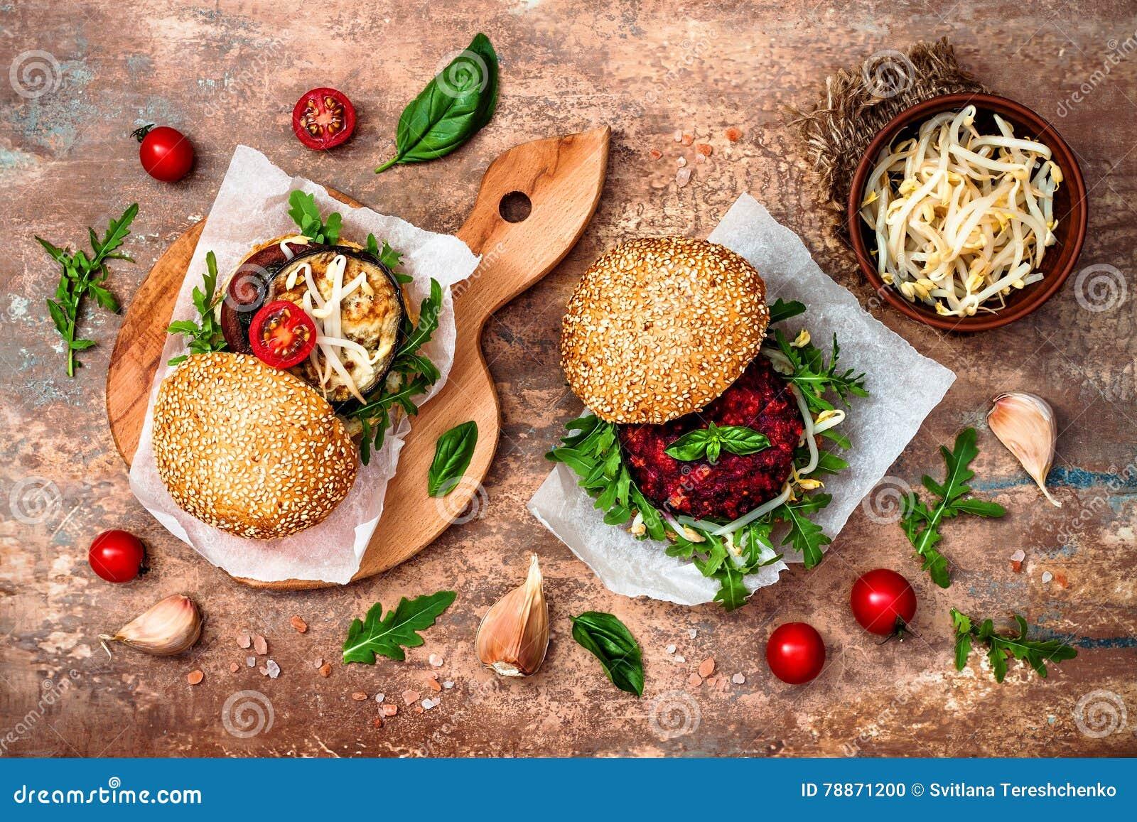 O vegetariano grelhou a beringela, a rúcula, os brotos e o hamburguer do molho do pesto Beterraba do vegetariano e hamburguer do