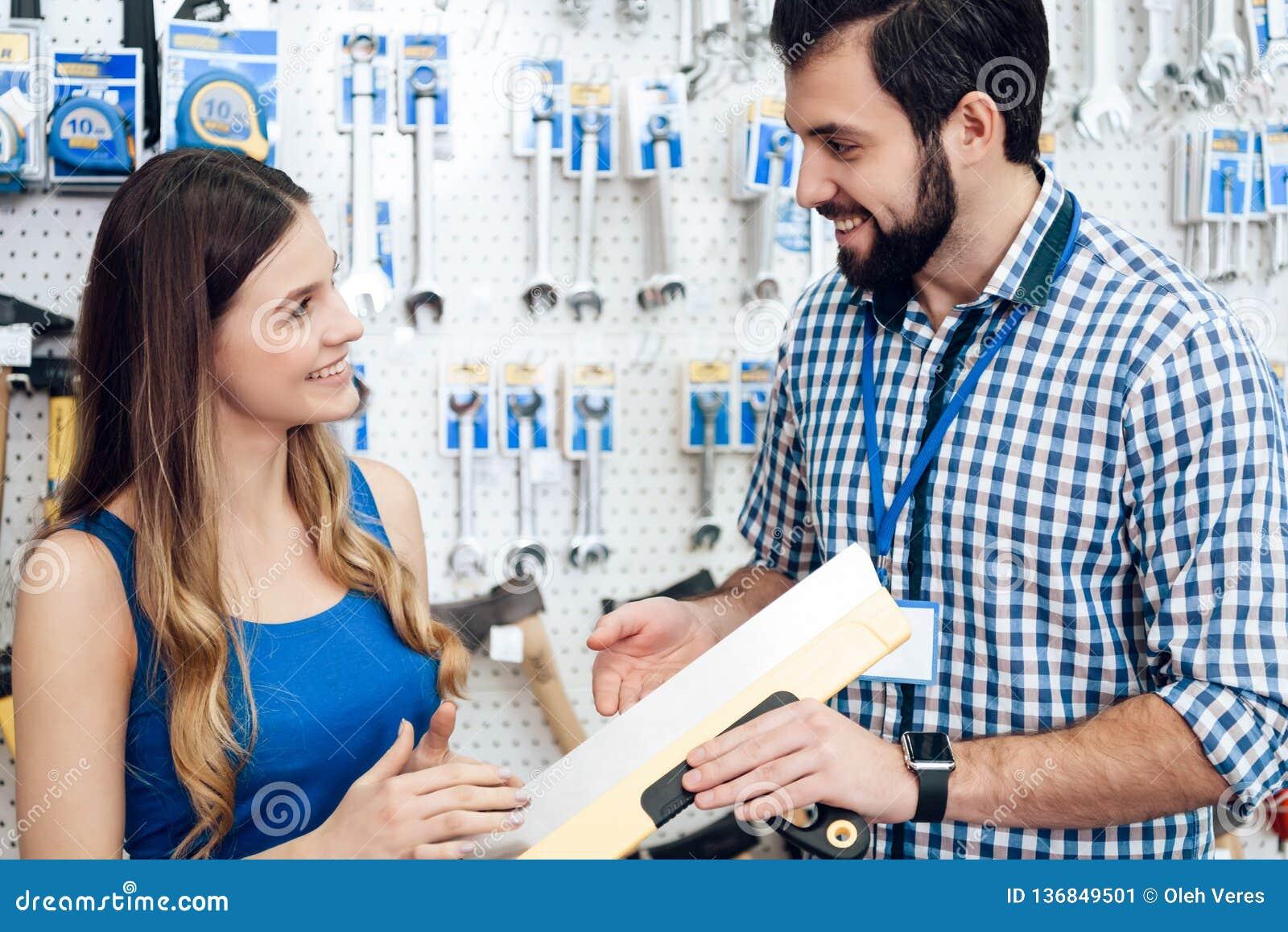 O vendedor está mostrando a espátula fêmea da massa de vidraceiro do cliente na loja das ferramentas elétricas