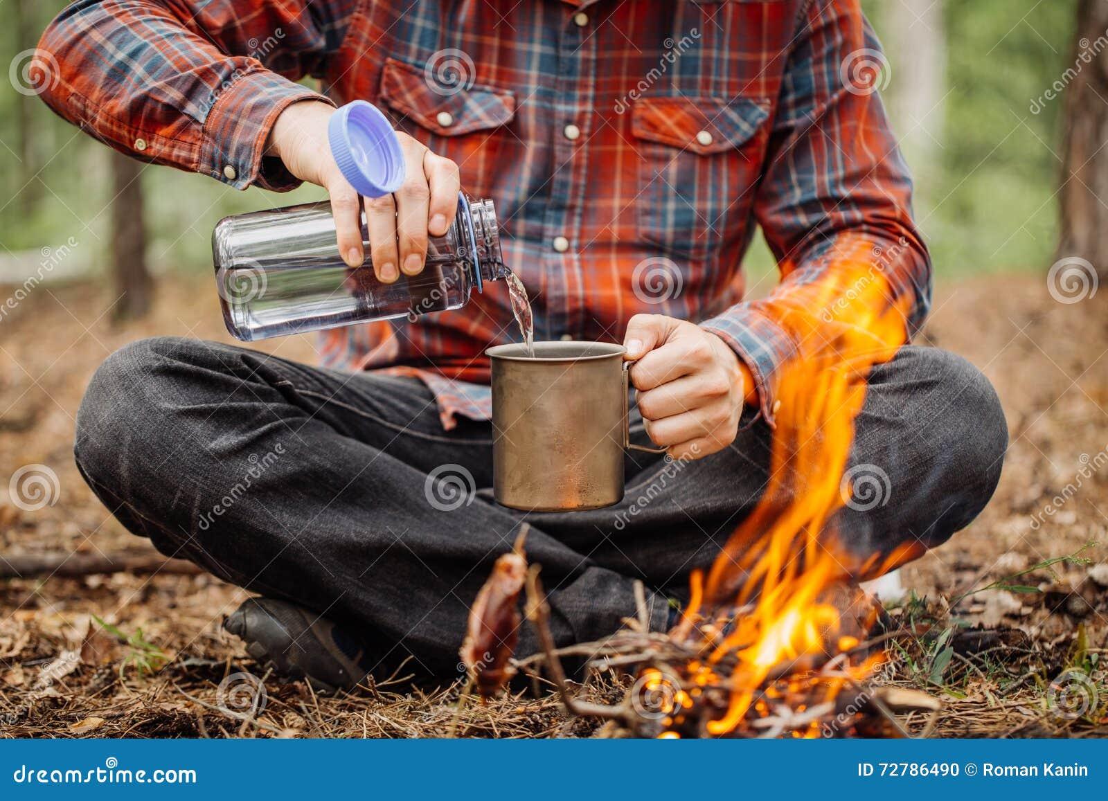 O viajante do homem derrama a água de uma garrafa em uma caneca do metal