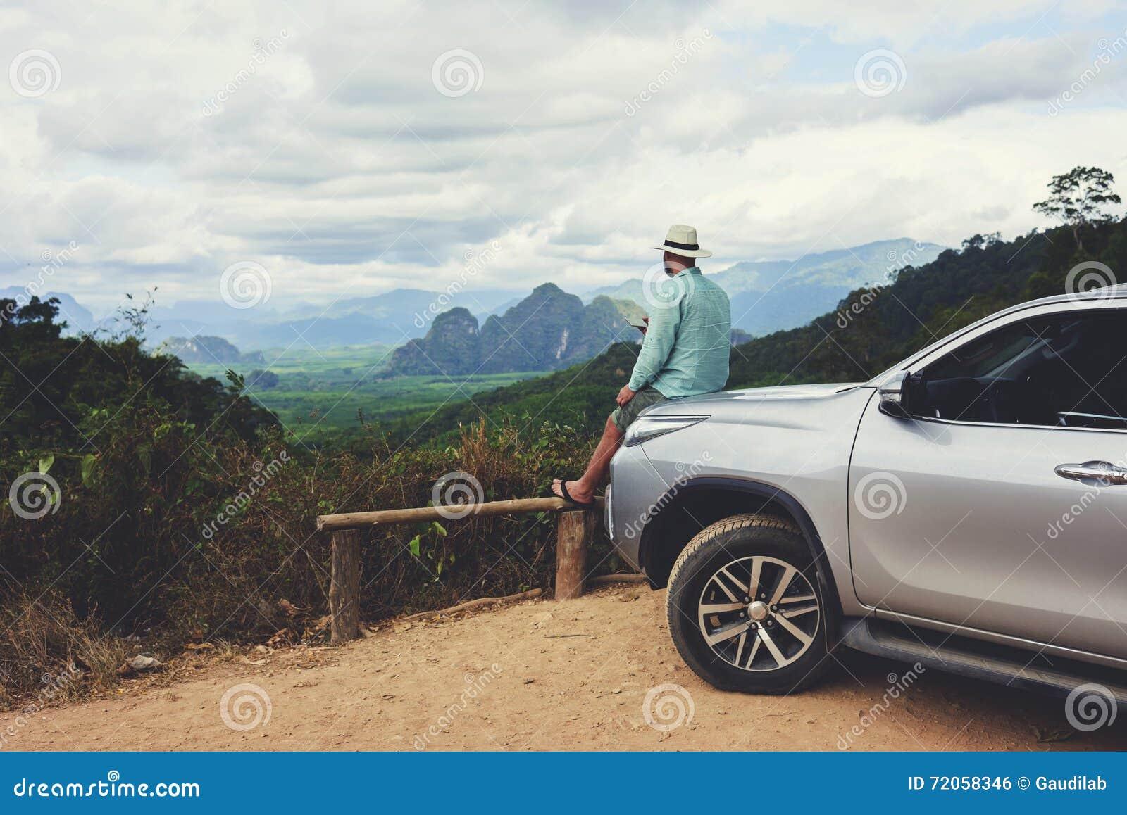 O viajante masculino está sonhando sobre algo, quando se sentar em uma capa do carro contra a opinião das Amazonas