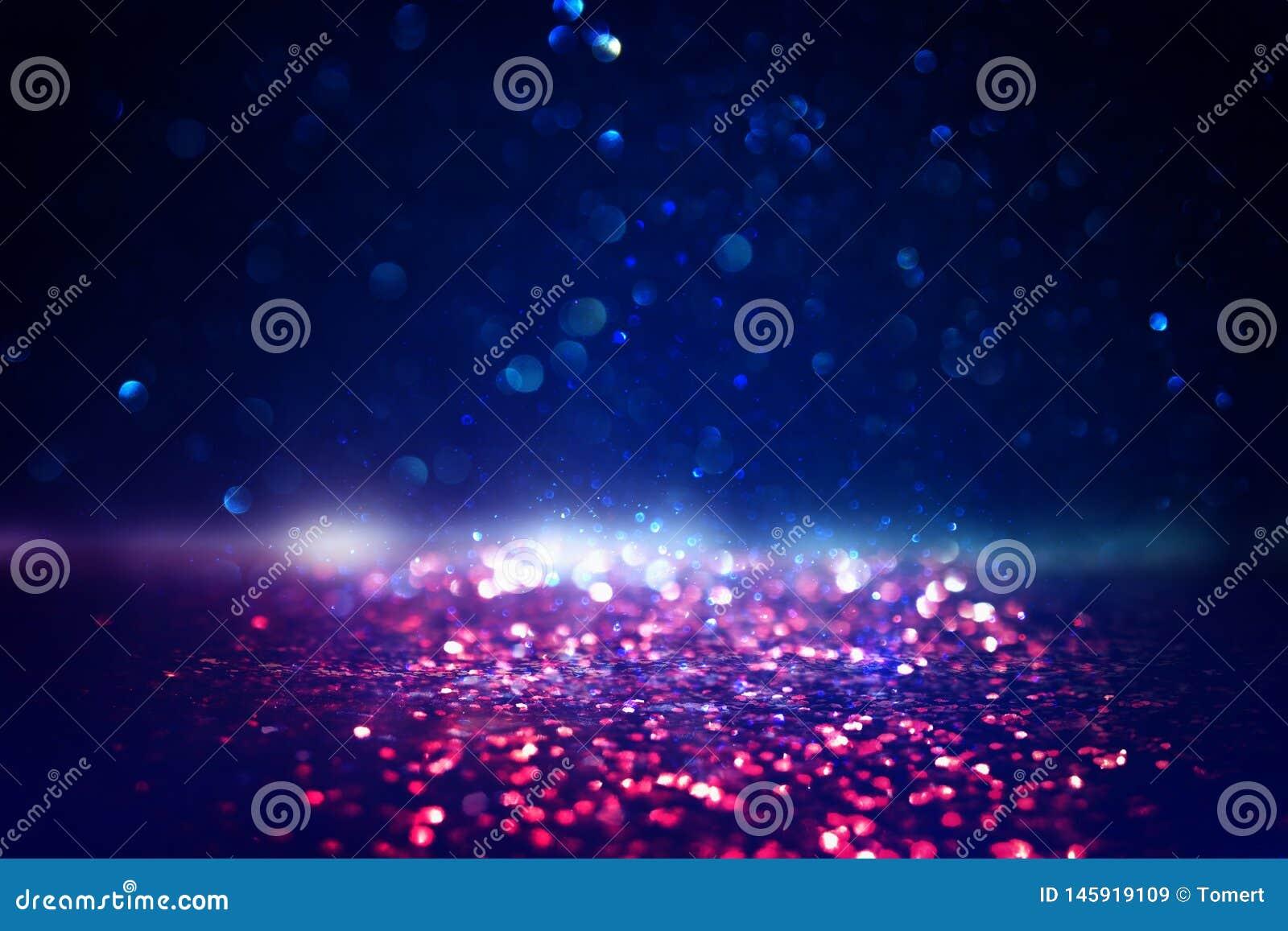 O vintage do brilho ilumina o fundo preto, ouro, roxo, azul e vermelho de-focalizado