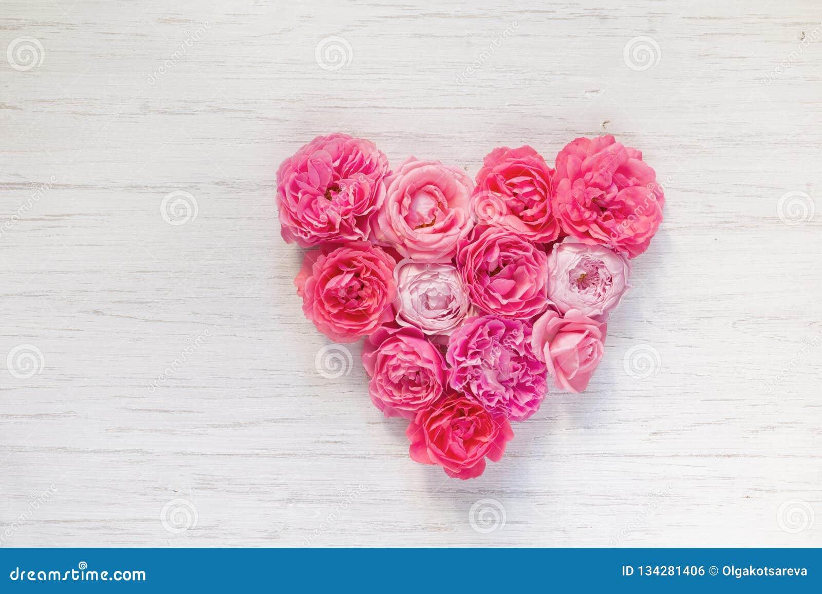 O vintage francês aumentou flores coração-dadas forma no fundo rústico de madeira branco Dia do `s do Valentim