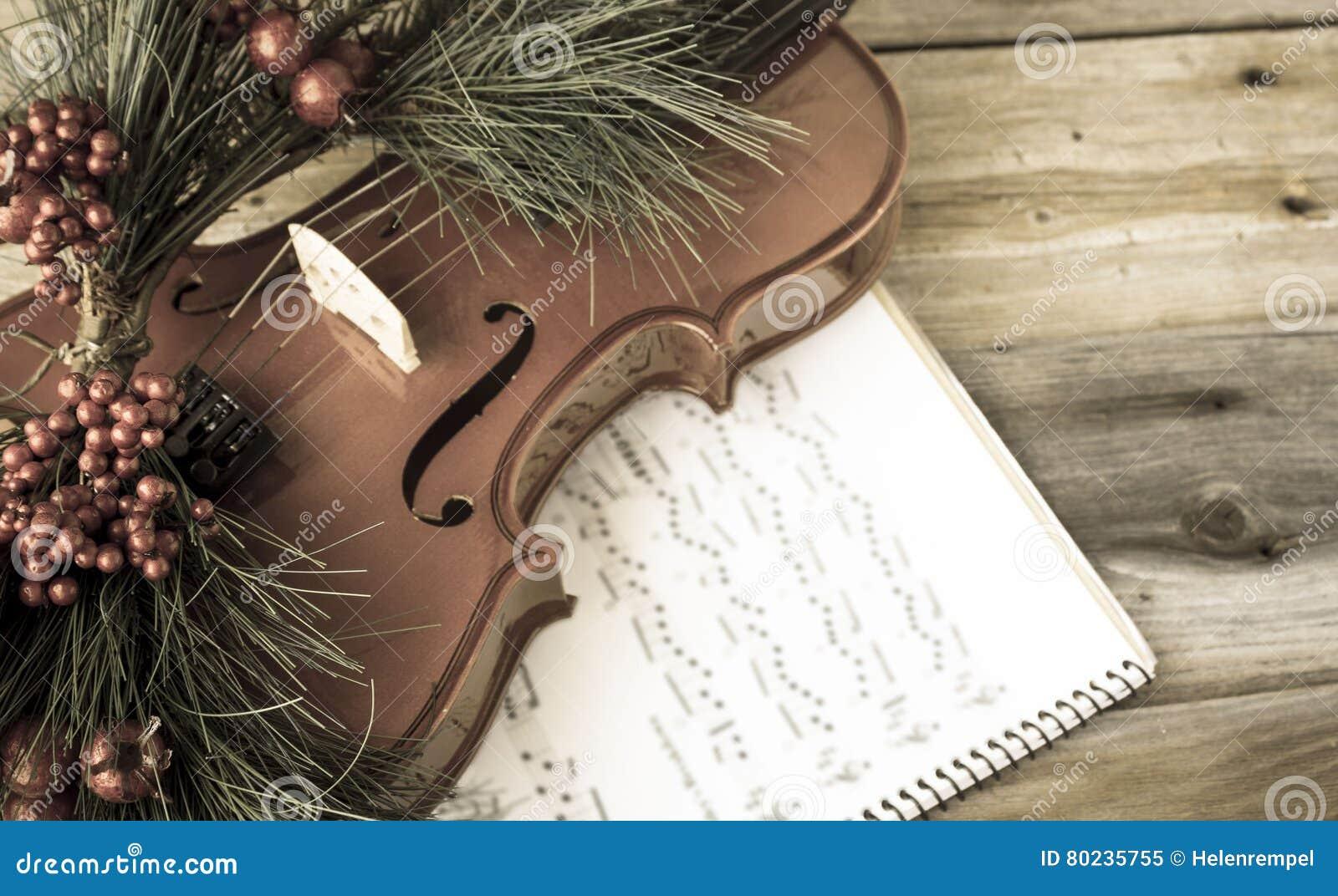 O violino do vintage decorou com a samambaia de Natal que encontra-se na partitura