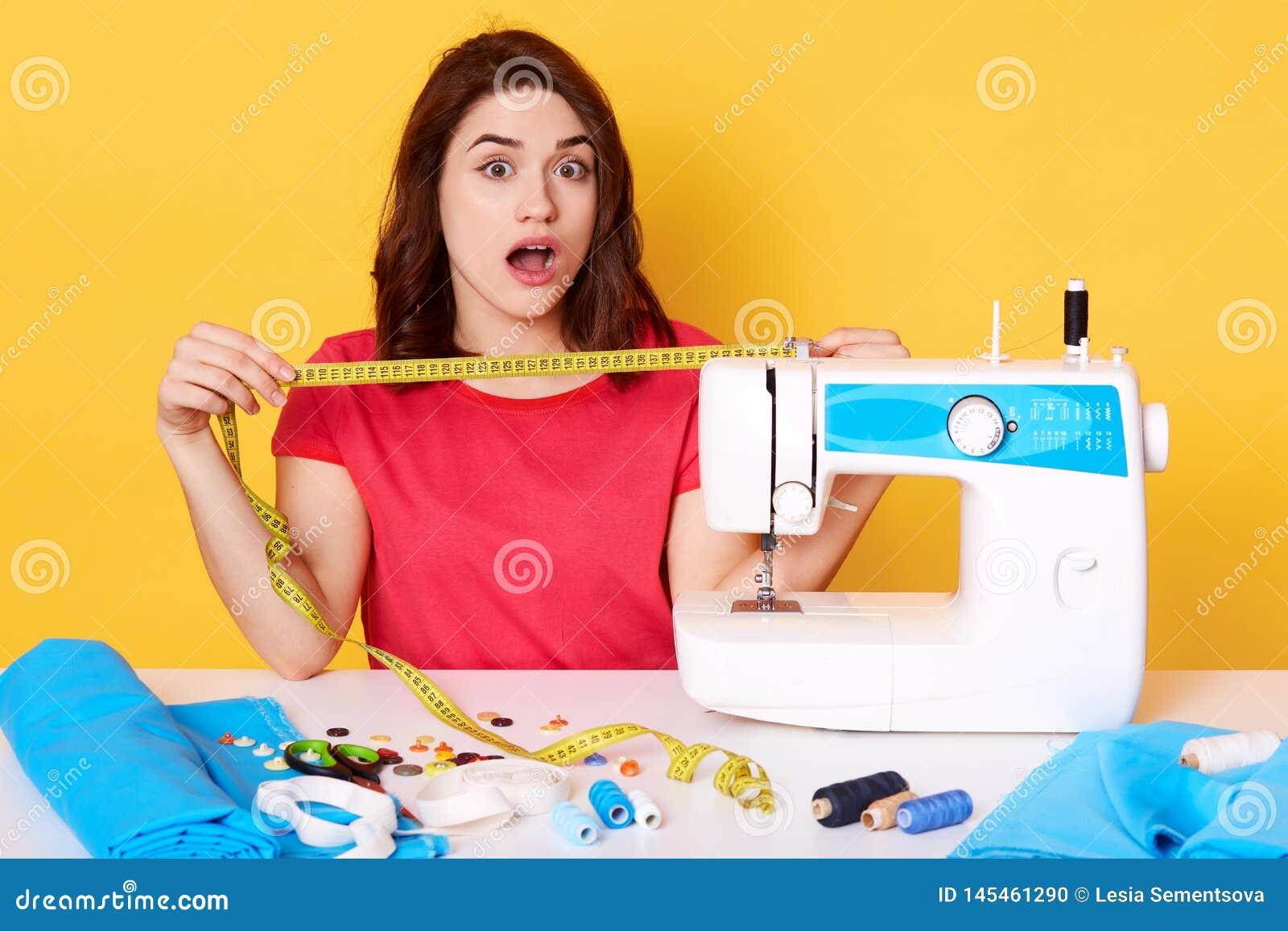O yuong bonito costura o trabalho na máquina de costura, não tem bastante pano, sentando-se com boca aberta, surpreendeu a expres