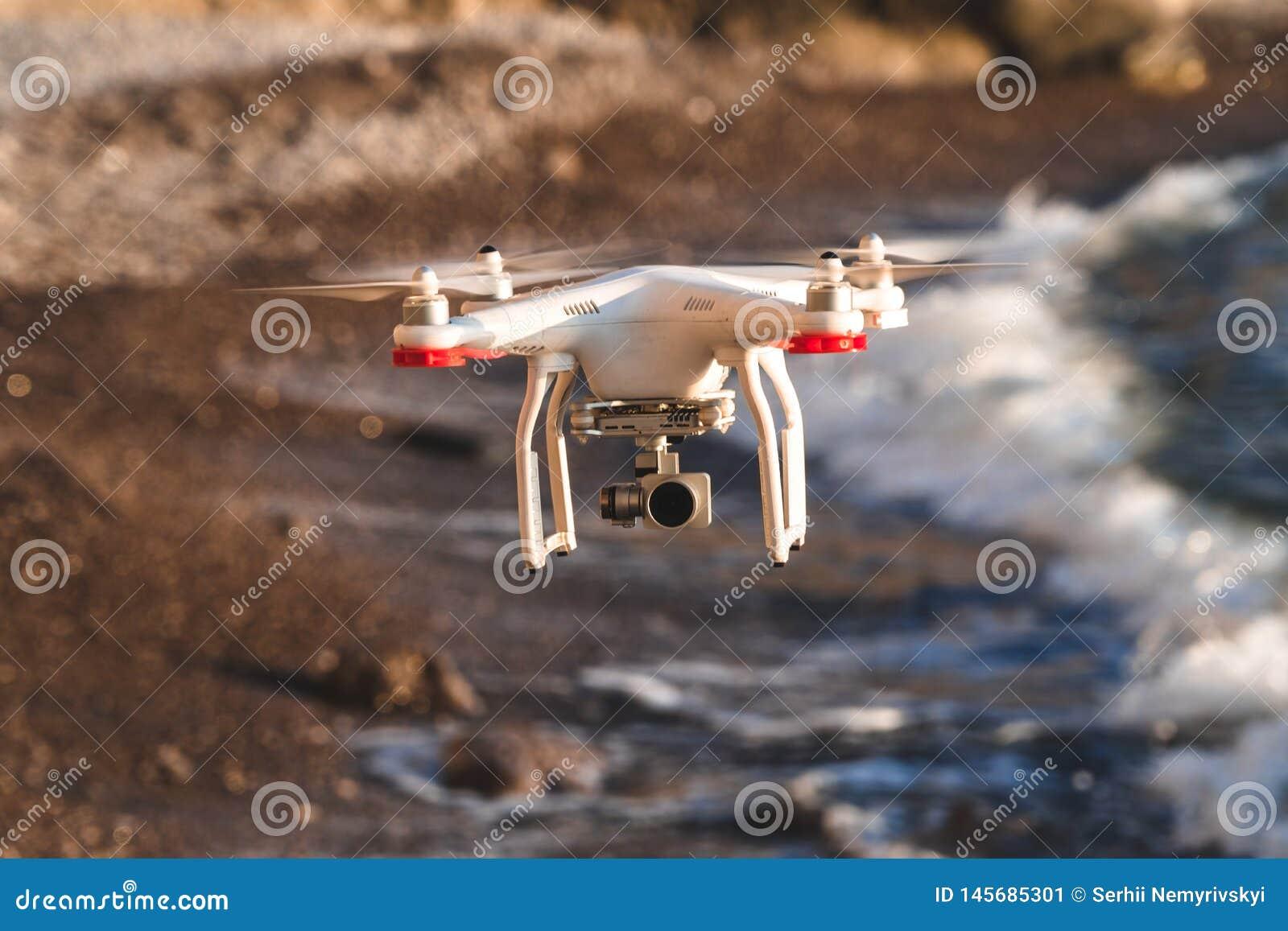 O zang?o no c?u do por do sol as montanhas da onda de oceano fecham-se acima do quadrocopter fora conceito para a videografia do