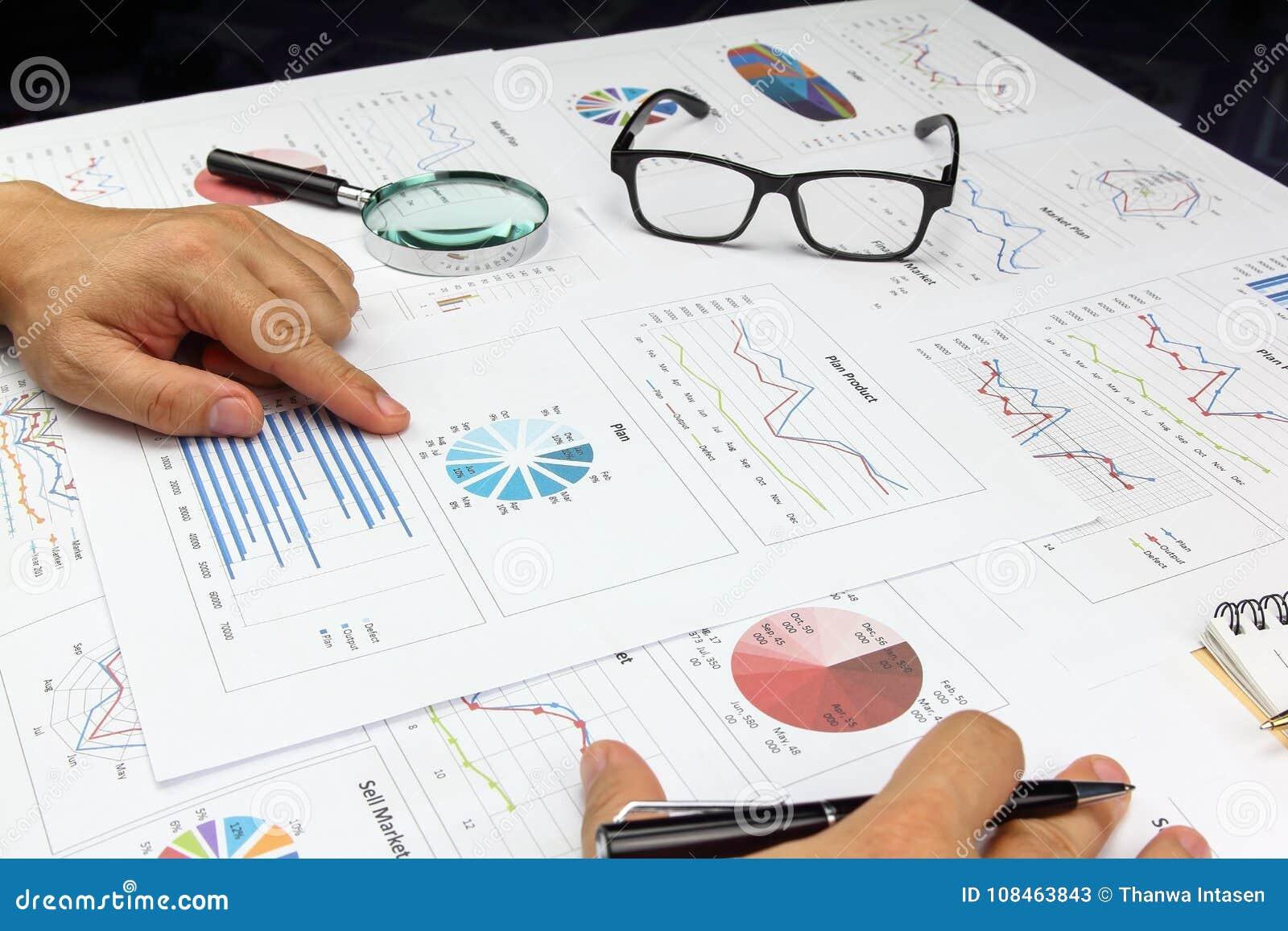 O zumbido da lupa do uso do homem de negócios e pensa analisa o gráfico