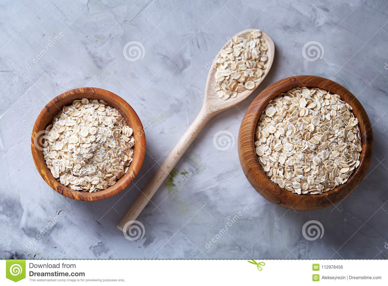 Oat flakes in bowl and wooden spoon on wooden background, close-up, top view, selective focus.