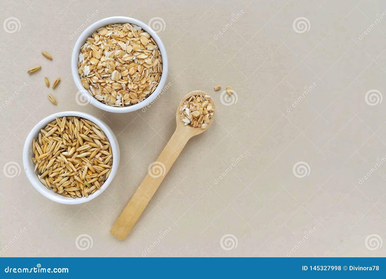 Oatmeal σε ένα ξύλινο κουτάλι και ολόκληρα σιτάρια των βρωμών