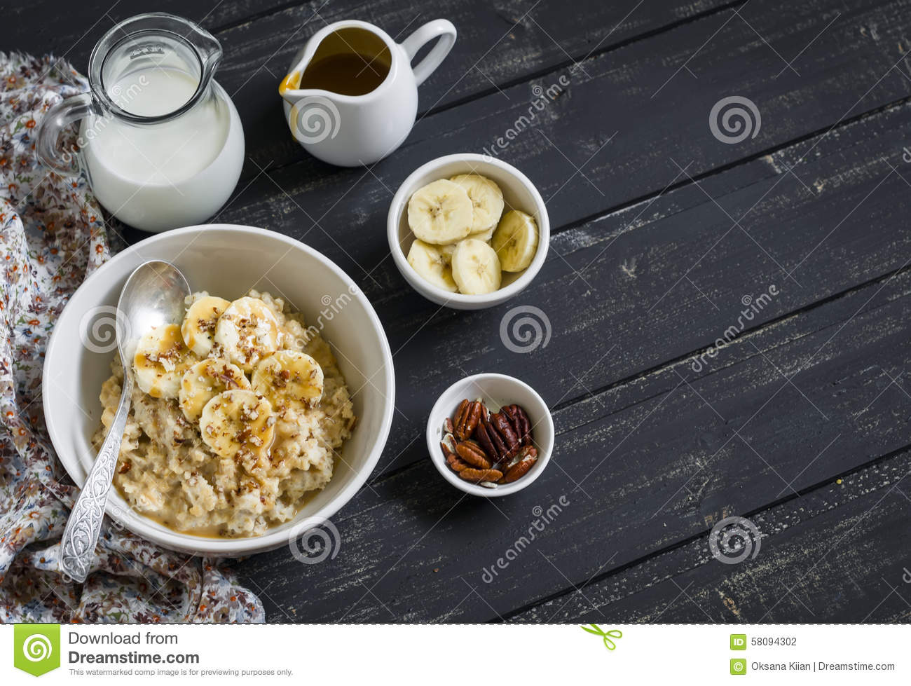 Oatmeal with banana, caramel sauce and pecan nuts in a white bowl on a dark wooden surface