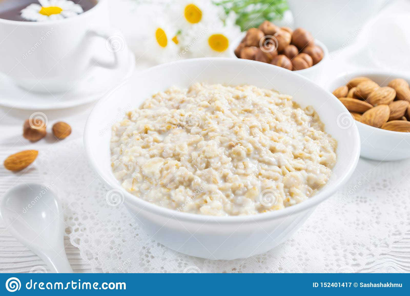 Oatmeal with nuts in bowl on white wooden table
