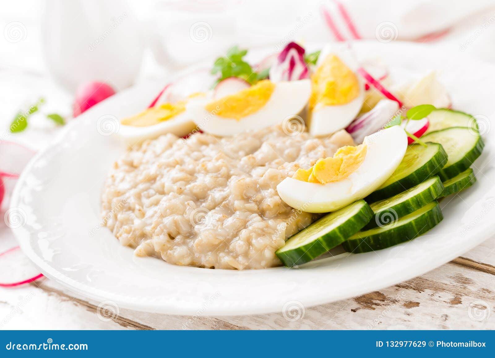 Oatmeal owsianka z gotowaną jajka, warzywa sałatką z i, śniadaniowy żywienioniowy zdrowy