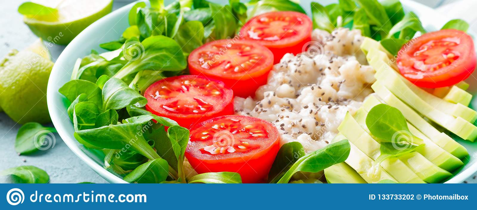 Oatmeal porridge with avocado and vegetable salad of fresh tomatoes and lettuce. Healthy dietary breakfast