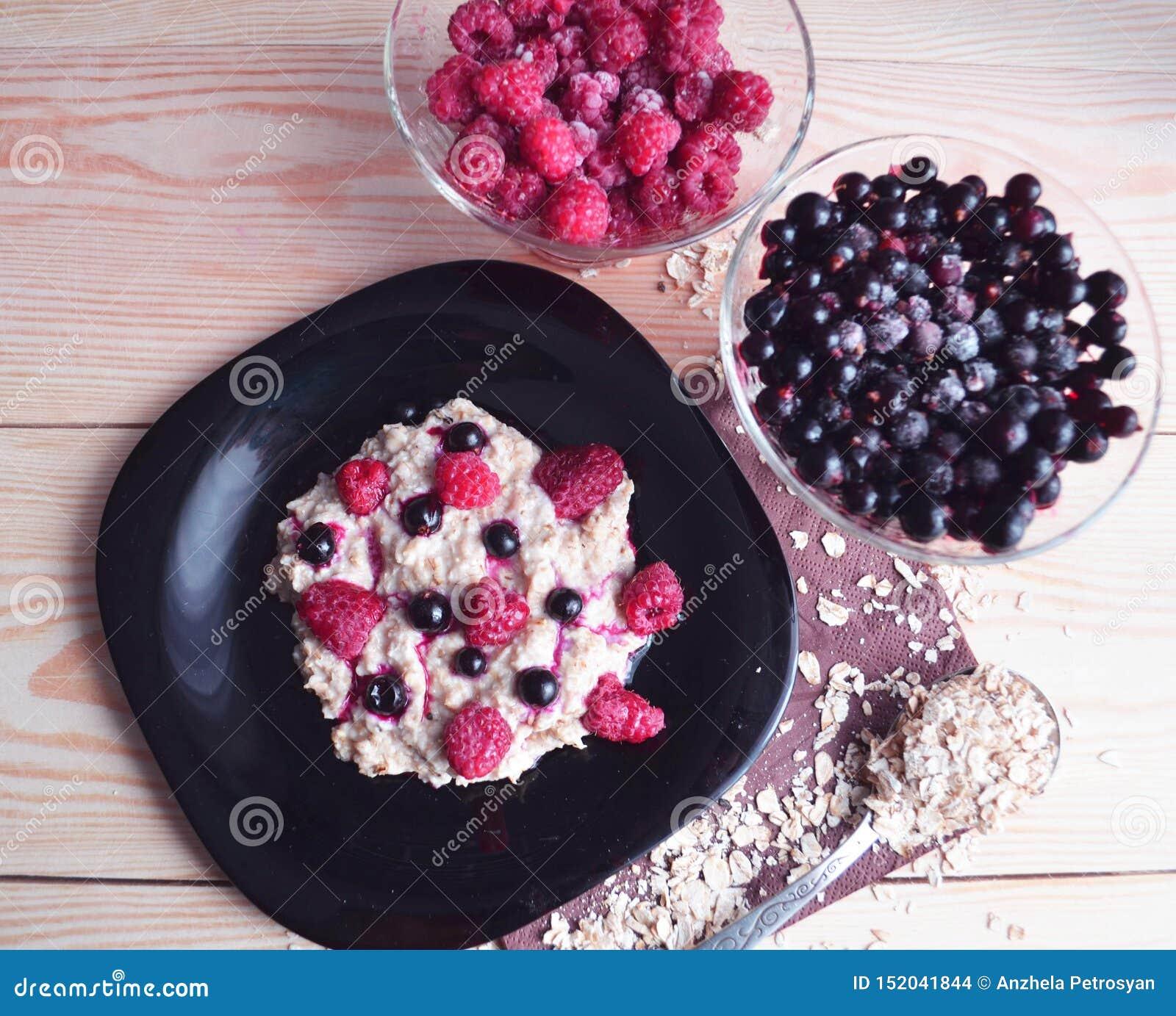 Oatmeal porridge with fresh raspberry and blueberry