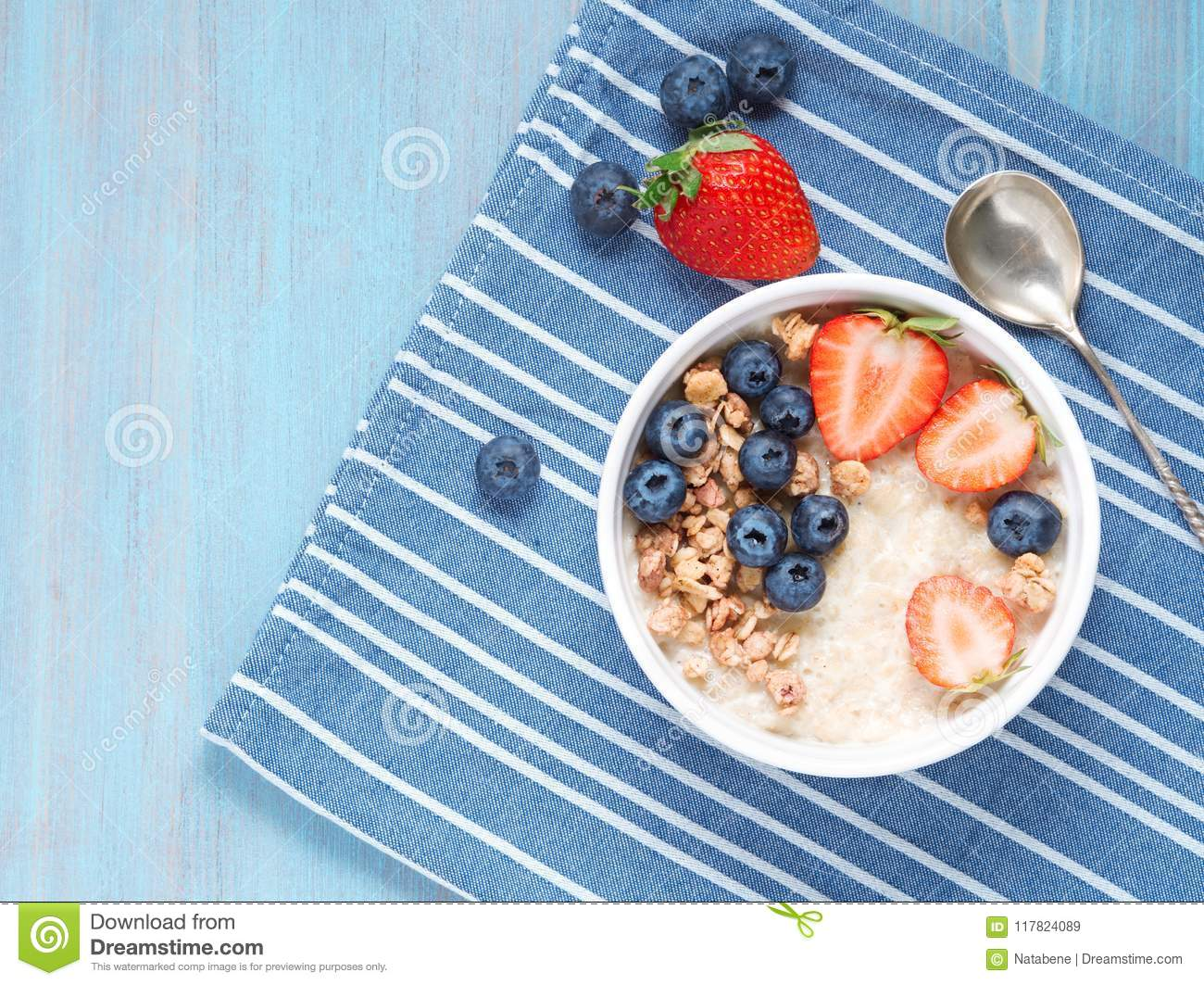 Oatmeal porridge with fresh strawberry, blueberry, granola on contrast blue background. Healthy breakfast. Top view.