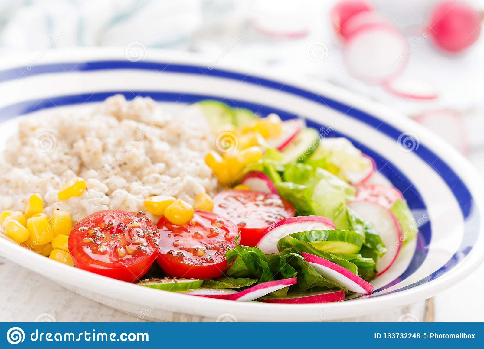 Oatmeal porridge with vegetable salad of fresh tomatoes, corn, cucumber and lettuce. Light, healthy and tasty dietary breakfast