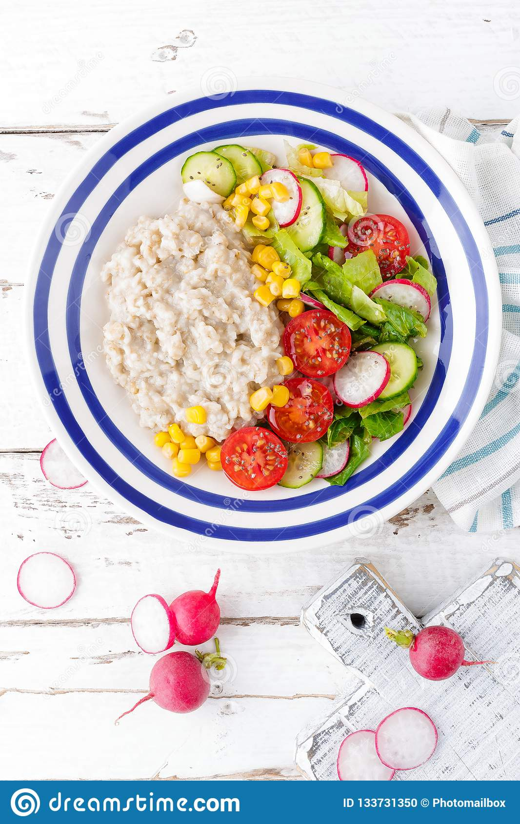 Oatmeal porridge with vegetable salad of fresh tomatoes, corn, cucumber and lettuce. Light, healthy and tasty dietary breakfast.