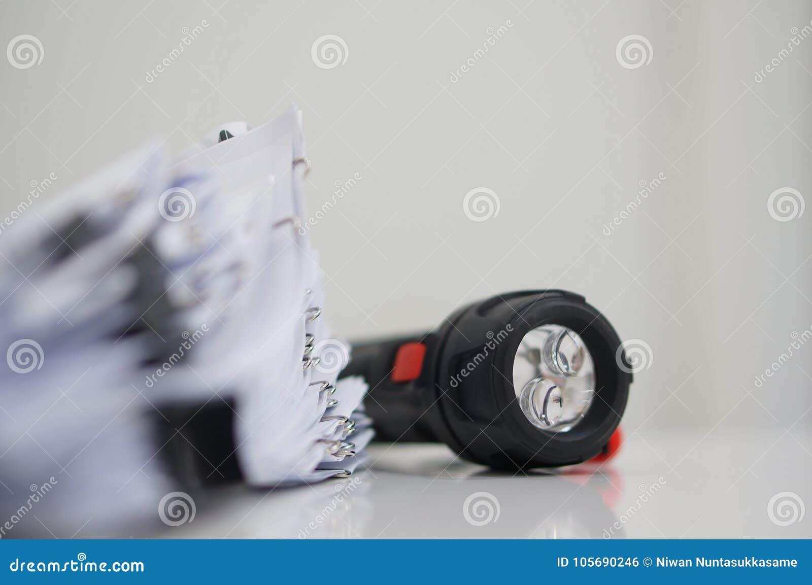 Oavslutat dokument med gem på skrivbordet för rapport och ficklampa