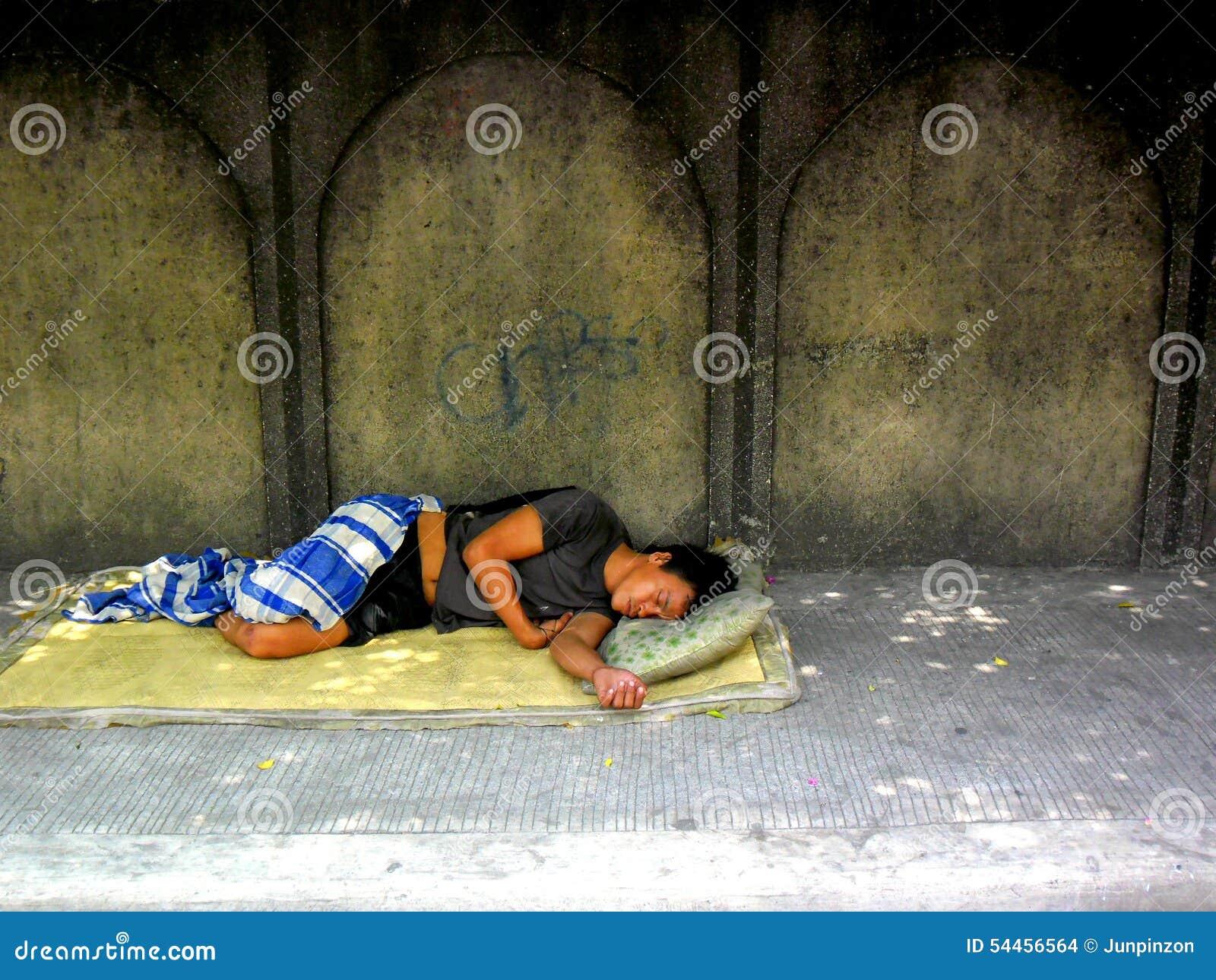 Obdachloser Mann, der auf einem Bürgersteig schläft