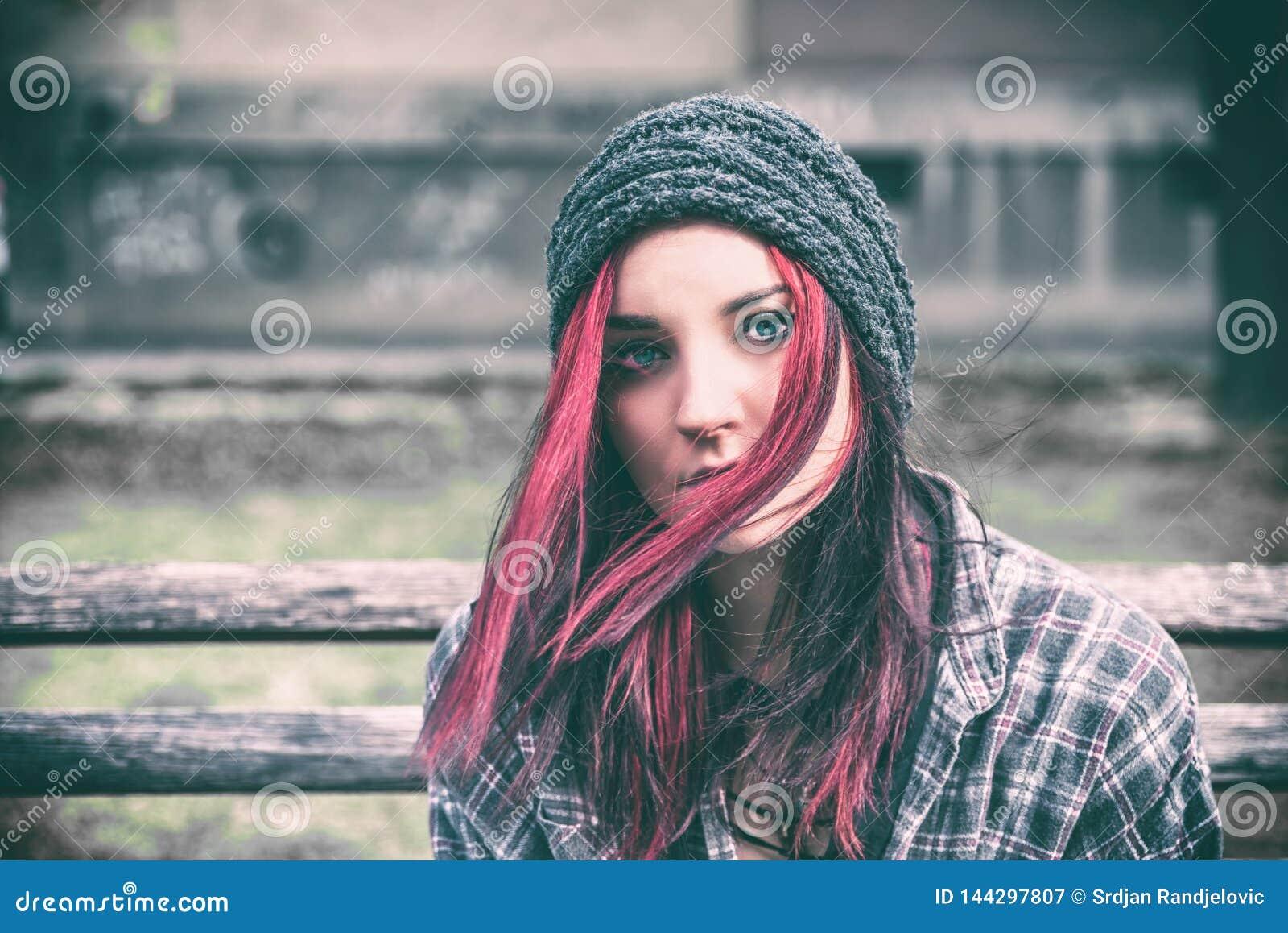 Obdachloses Mädchen, junges rotes Haarmädchen, das allein draußen mit Hut sitzen und Hemd besorgt und deprimiert, nachdem sie ein