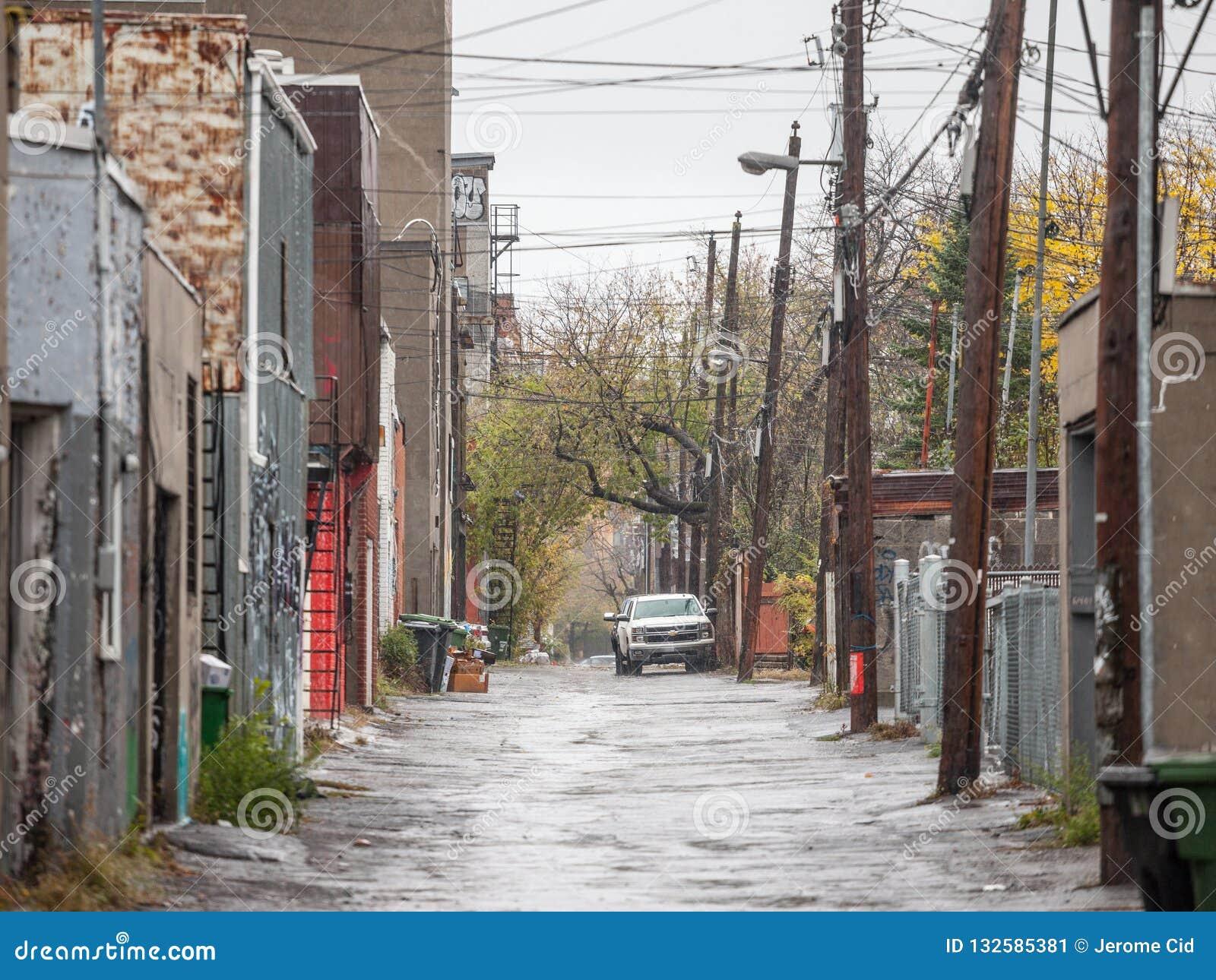 Obdrapana typowa północnoamerykańska mieszkaniowa ulica w jesieni w Montreal, Quebec, podczas deszczowego dnia z samochodami park