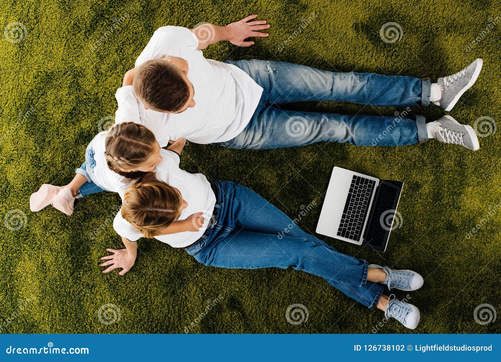 Obenliegende Ansicht der Familie mit dem Laptopstillstehen