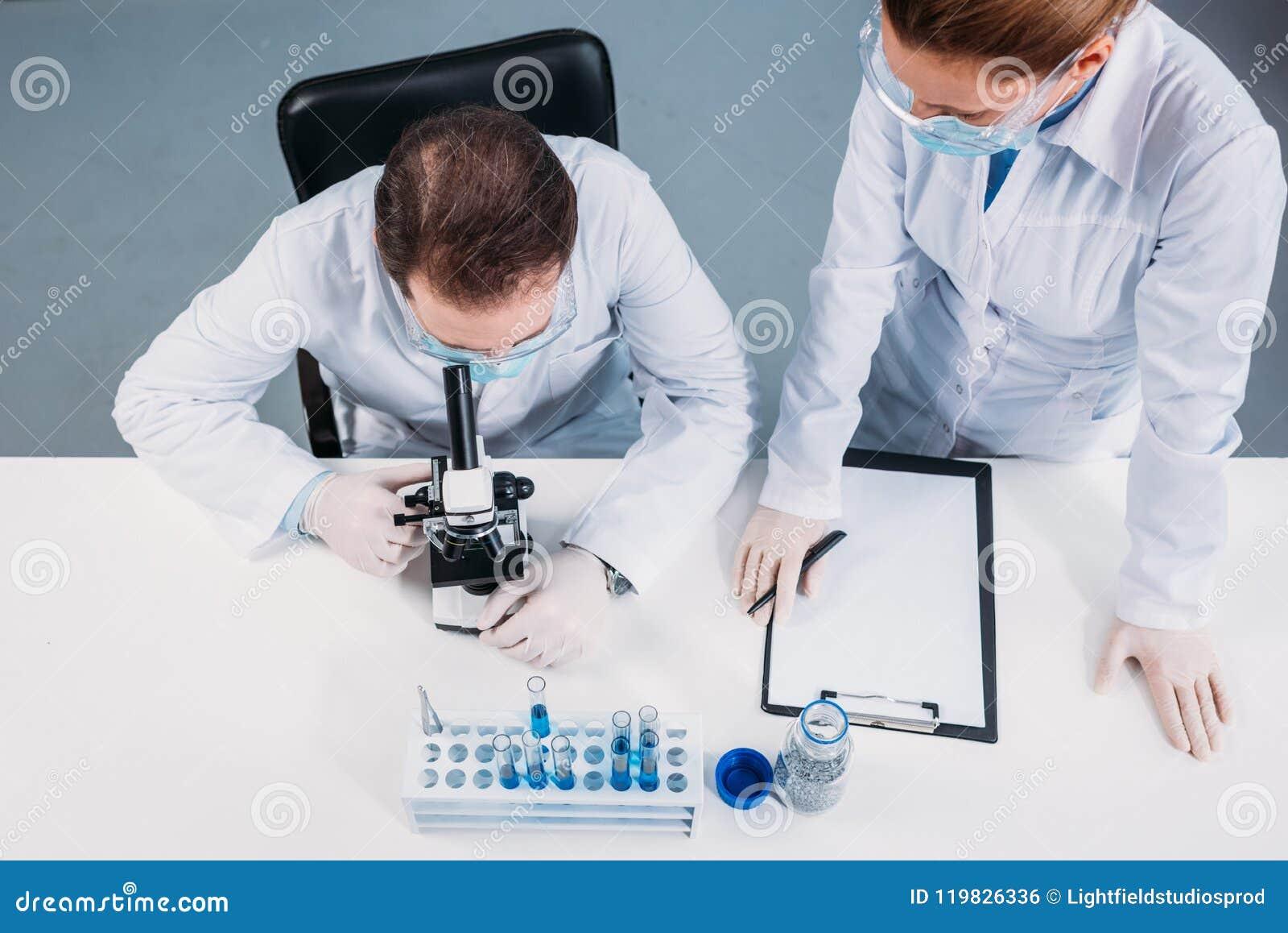 Obenliegende Ansicht von Wissenschaftlern in den medizinischen Masken und von Schutzbrillen, die an wissenschaftlicher Forschung