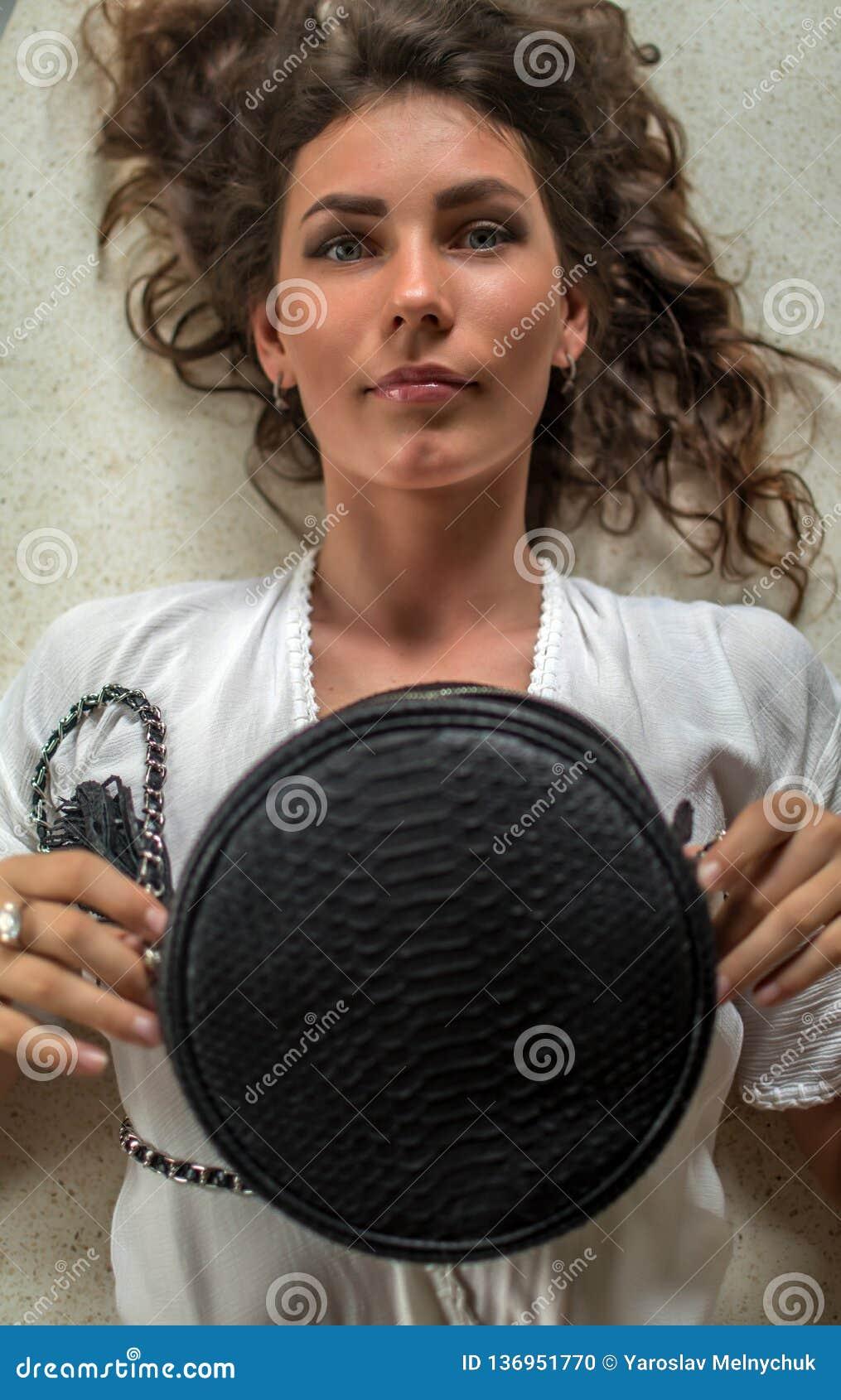 Obenliegende Porträtansicht einer schönen jungen Frau, die in ihrem teuren Landhaus mit luxuty Pythonschlangentasche niederlegt H