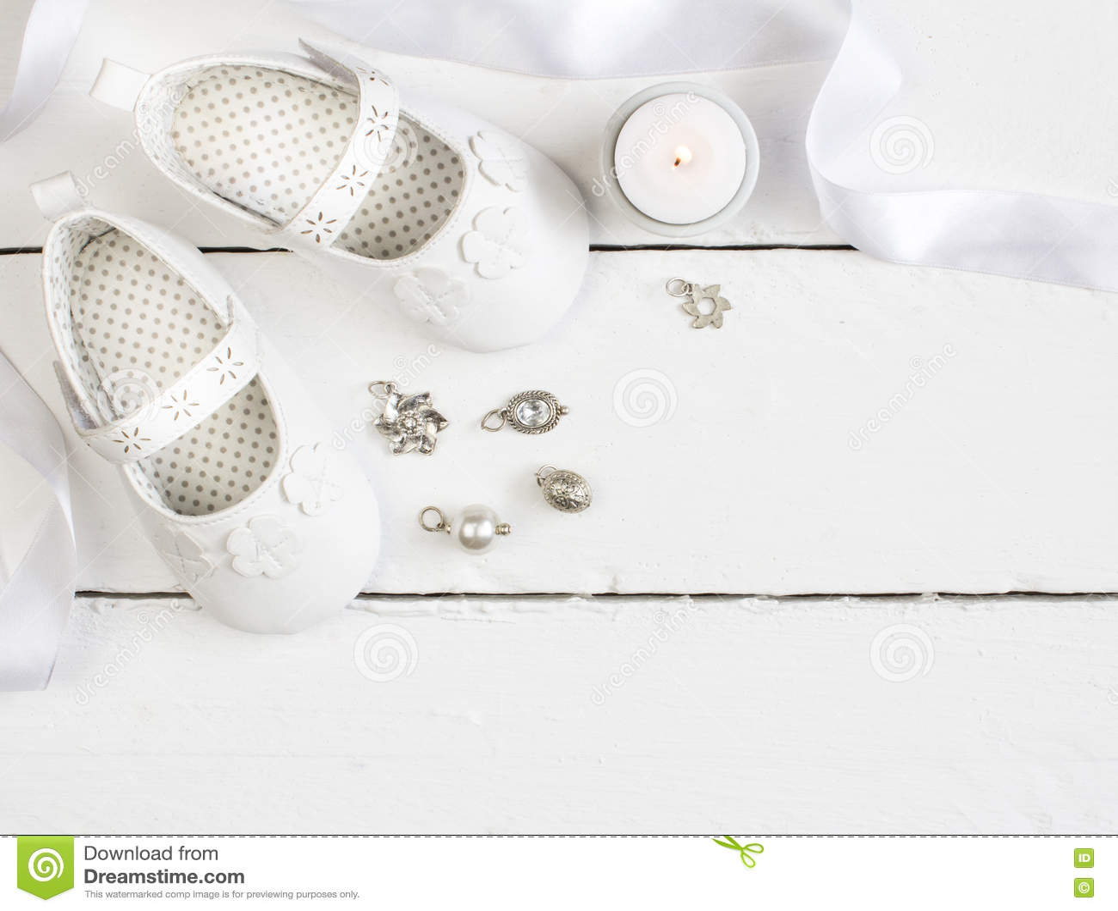 Obenliegendes Foto von Paaren der weißen Babybeuten, Kerze, Band und
